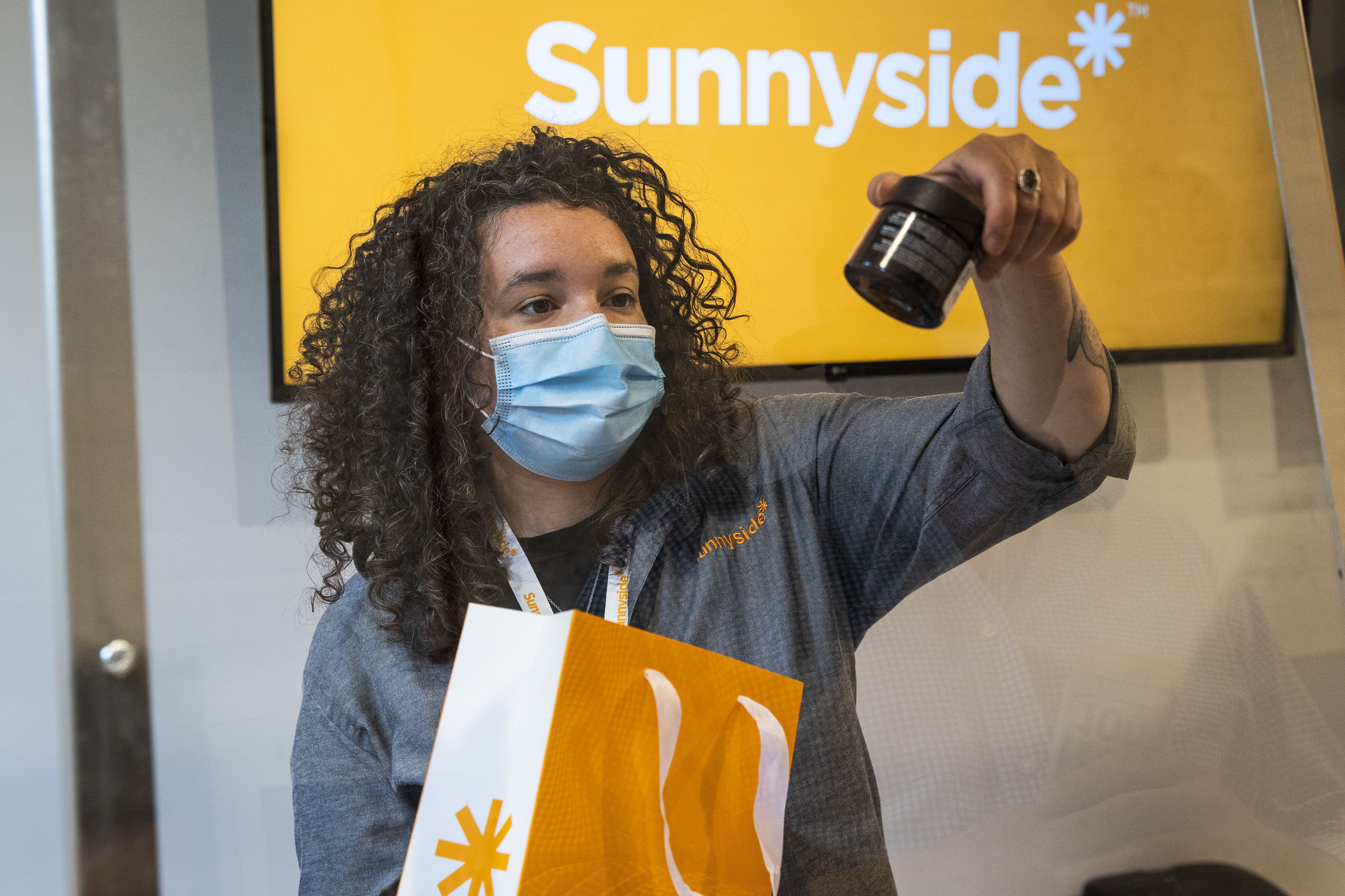 Jordan Davis, a wellness advisor, shows products to a 55-year-old man from River North as he makes the second purchase at Cresco Labs' seventh Sunnyside dispensary at 436 N. Clark St. on the store's opening day in River North, Thursday morning, May 28, 2020.