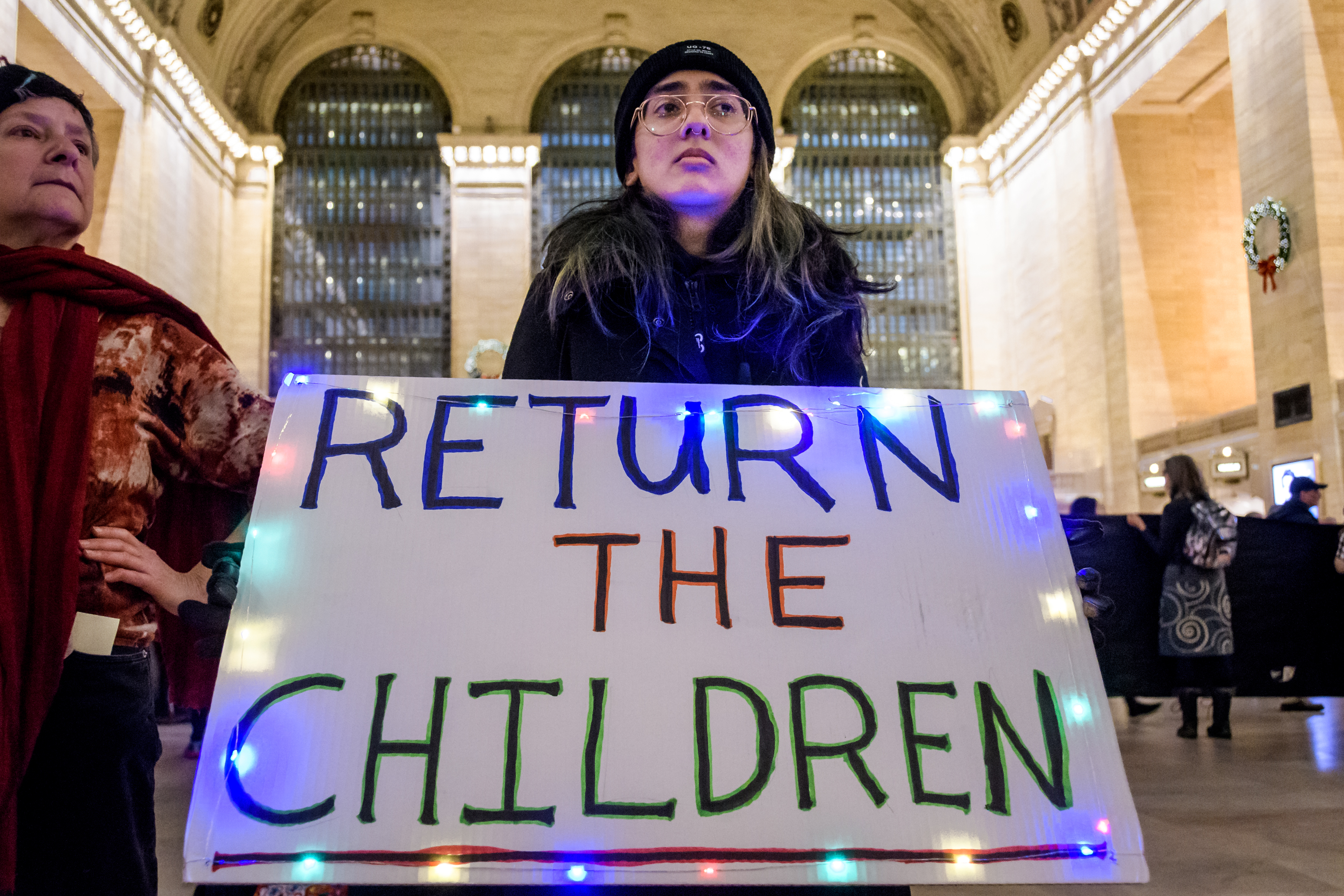"The protester is holding a sign reading, ""Return the children."""