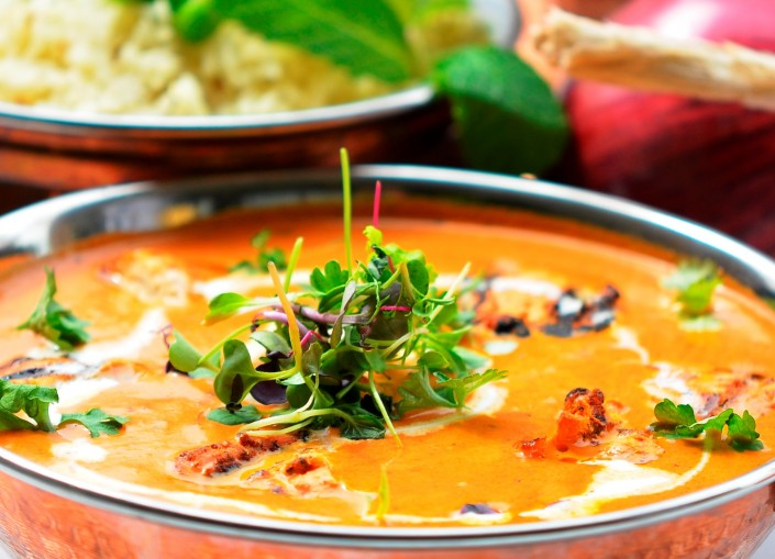 A bowl of orange curry with microgreens on top from Marigold Maison.