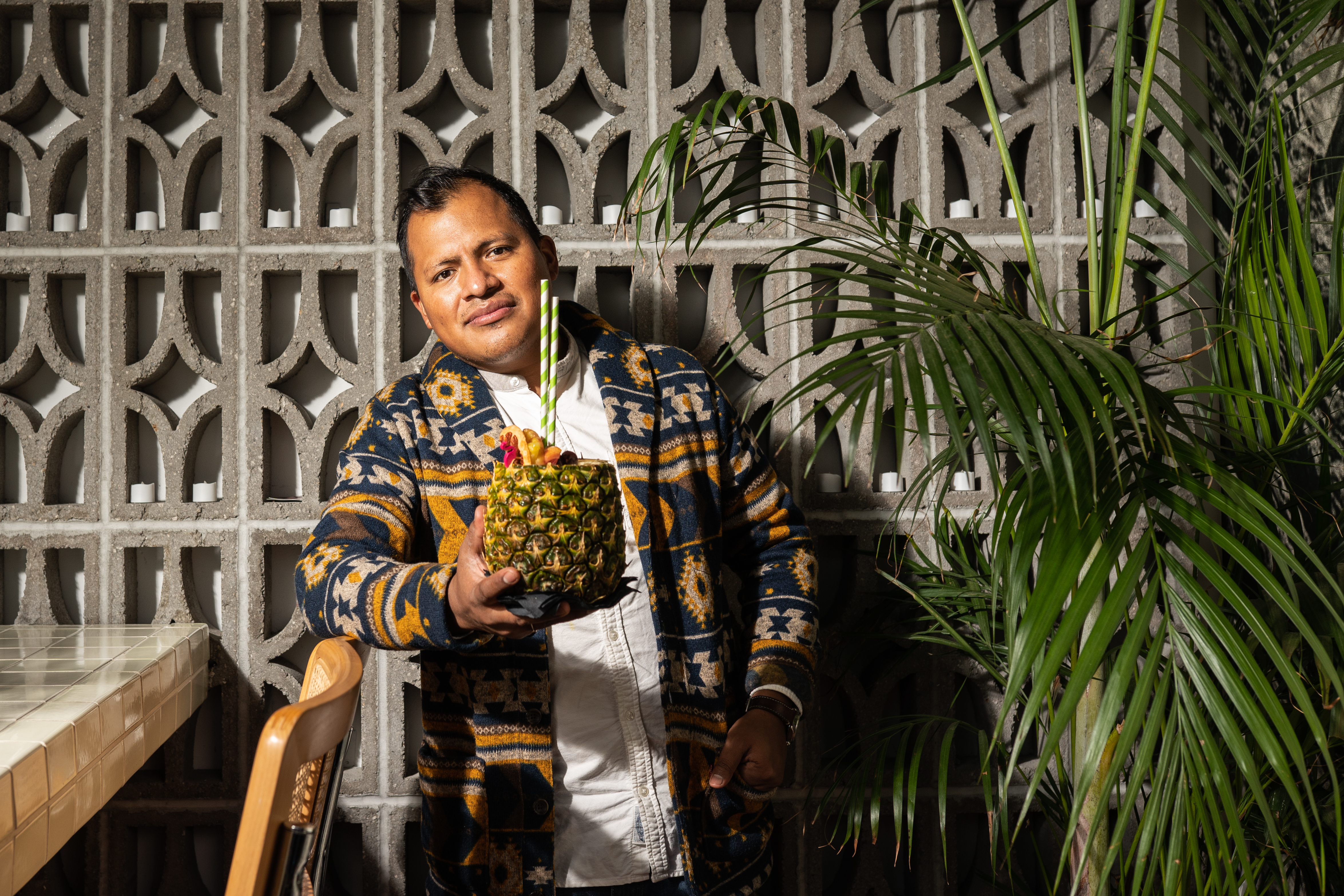Alfredo holds a piña colada in his hand,