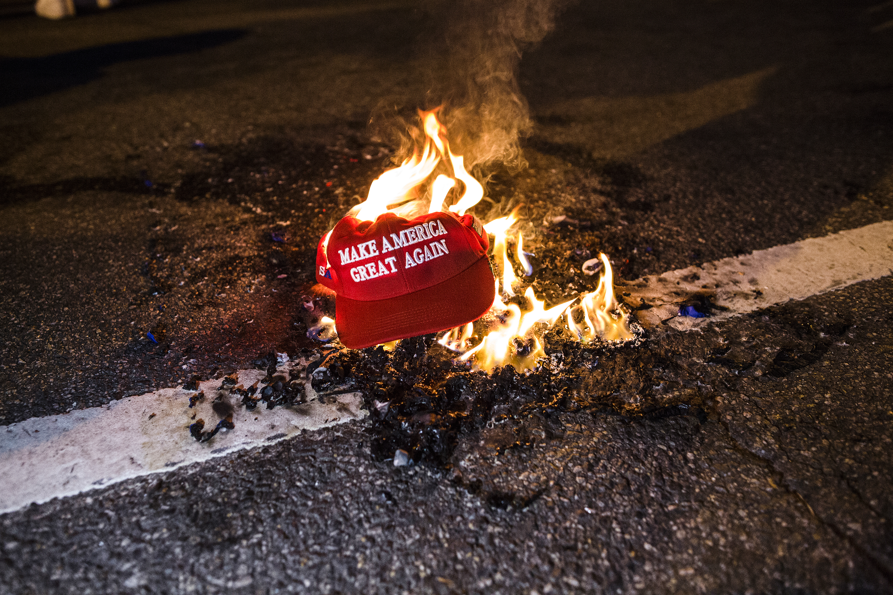 A red MAGA hat on fire in the road.