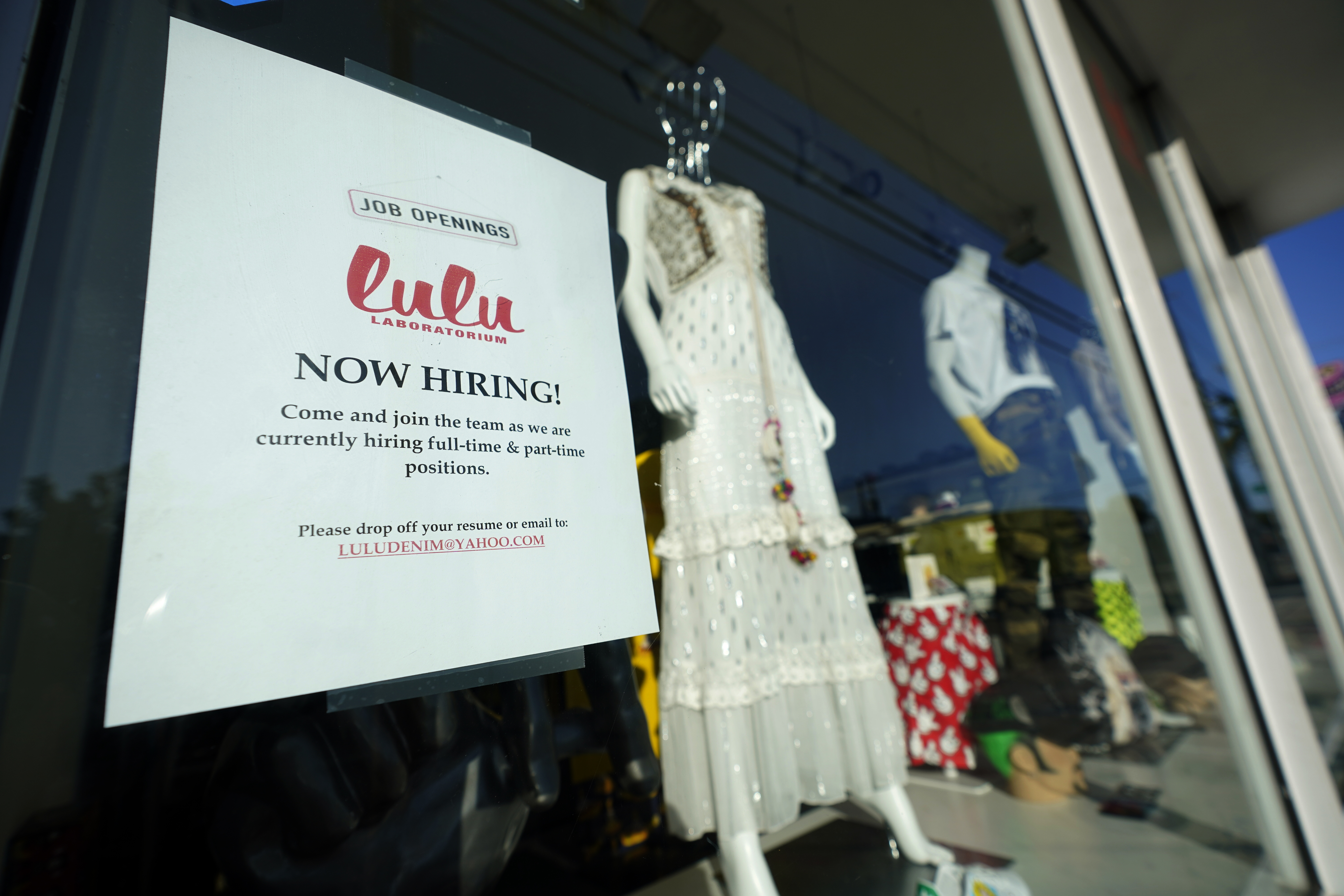 """A """"Now Hiring"""" sign is shown in the window of a store, Wednesday, Jan. 27, 2021, in the Wynwood Arts District of Miami."""