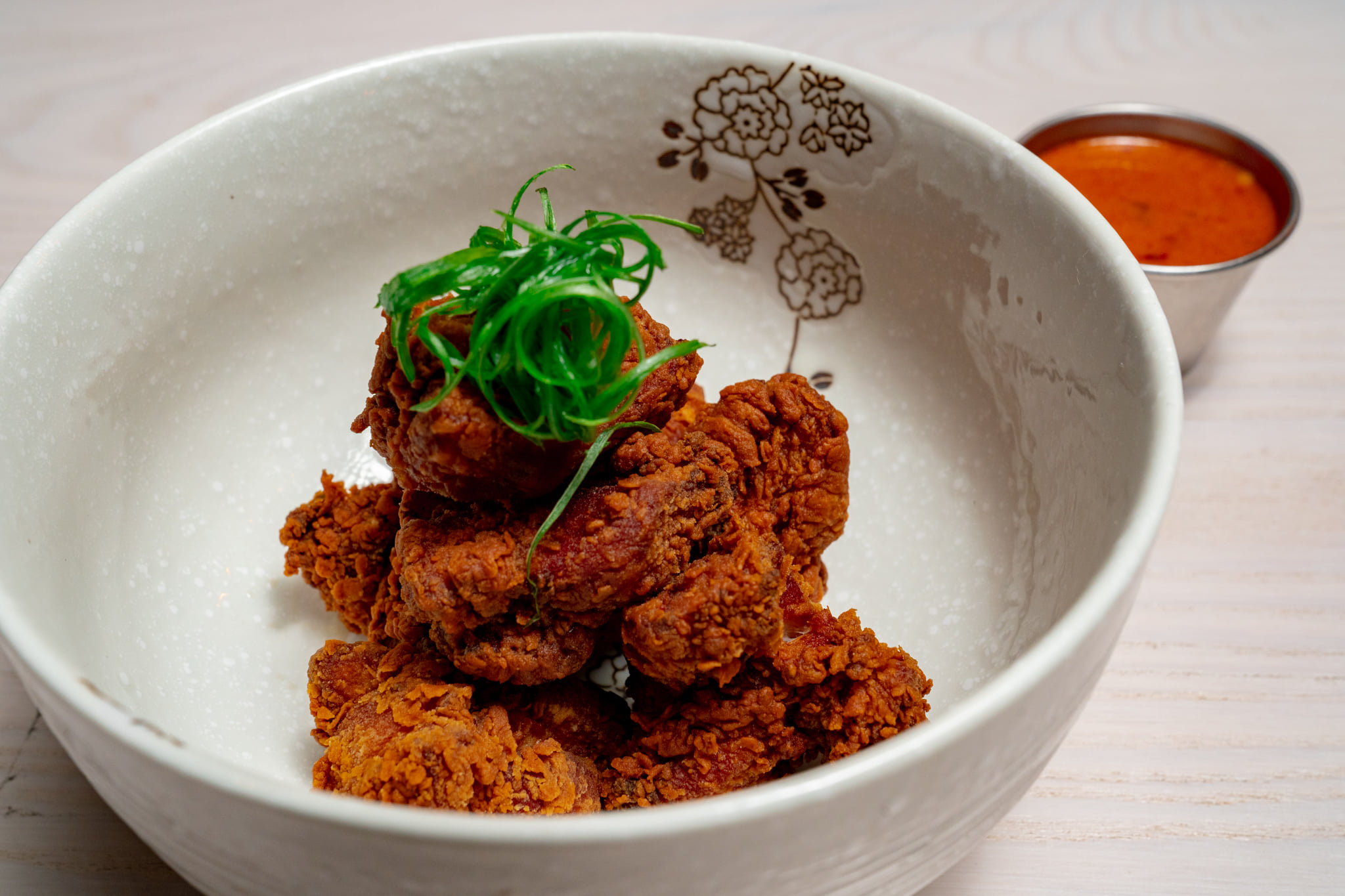 a bowl of fried chicken garnishes with shaved scallion and a side of red dipping sauce