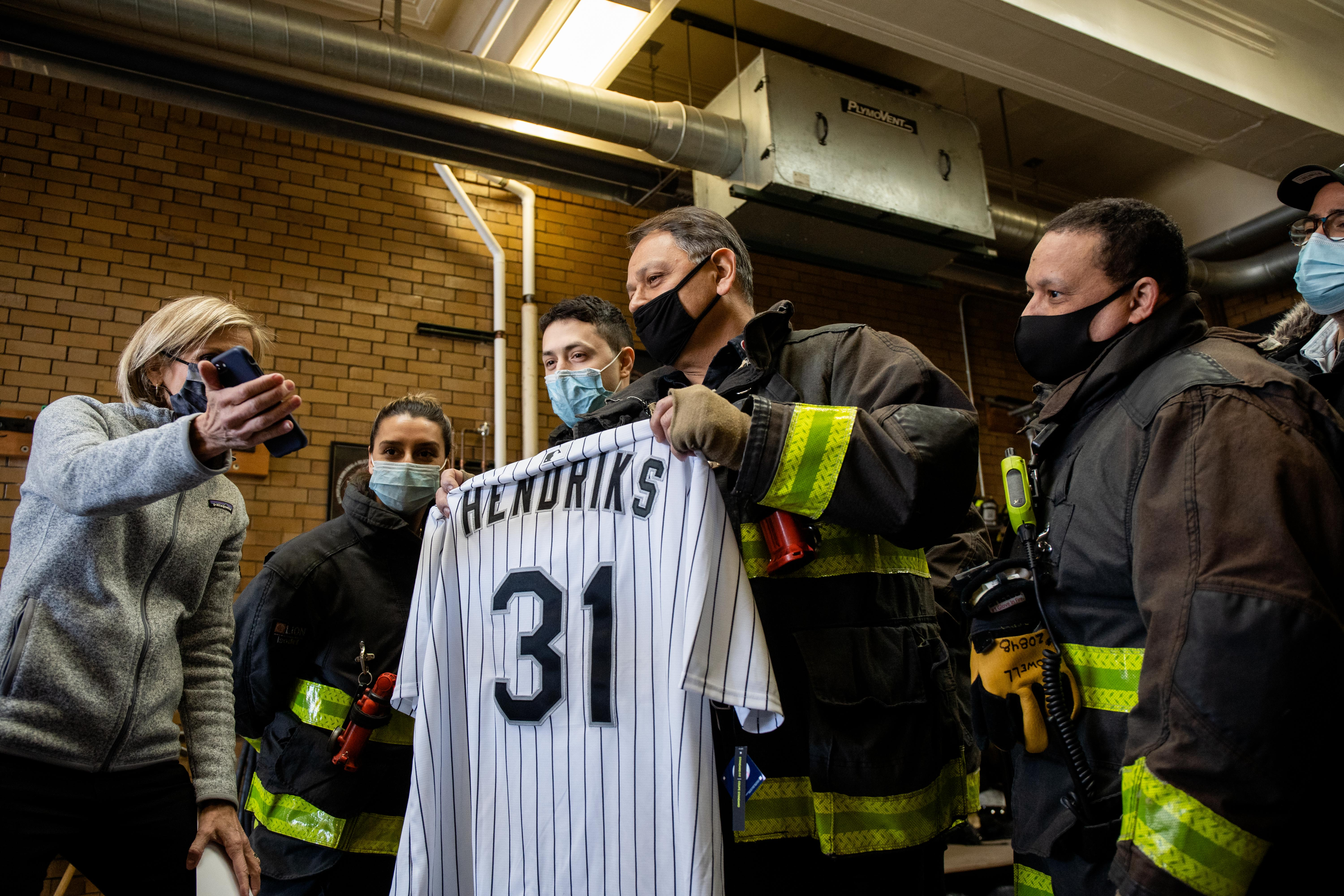 Chicago Fire Department firefighters at Engine 29 in Bridgeport watch a video of White Sox pitcher Liam Hendriks and his wife, who thanked them for their service, Thursday morning. The couple donated food from local restaurants to the firefighters.