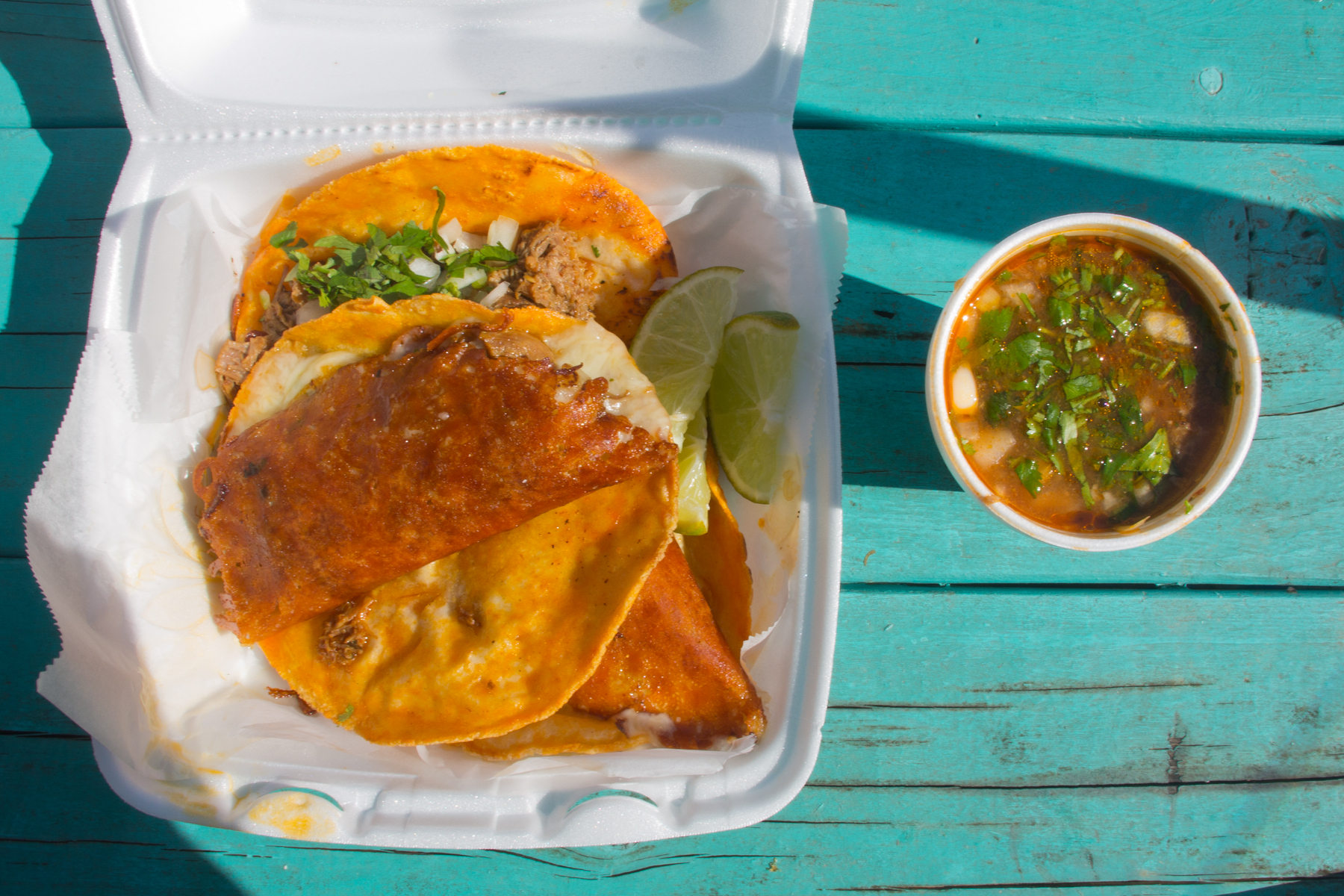 Tacos with cheese, meat, cilantro, and onions on white styrofoam food container on the left with a white styrofoam cup of consomme on the right on top of a teal-blue table