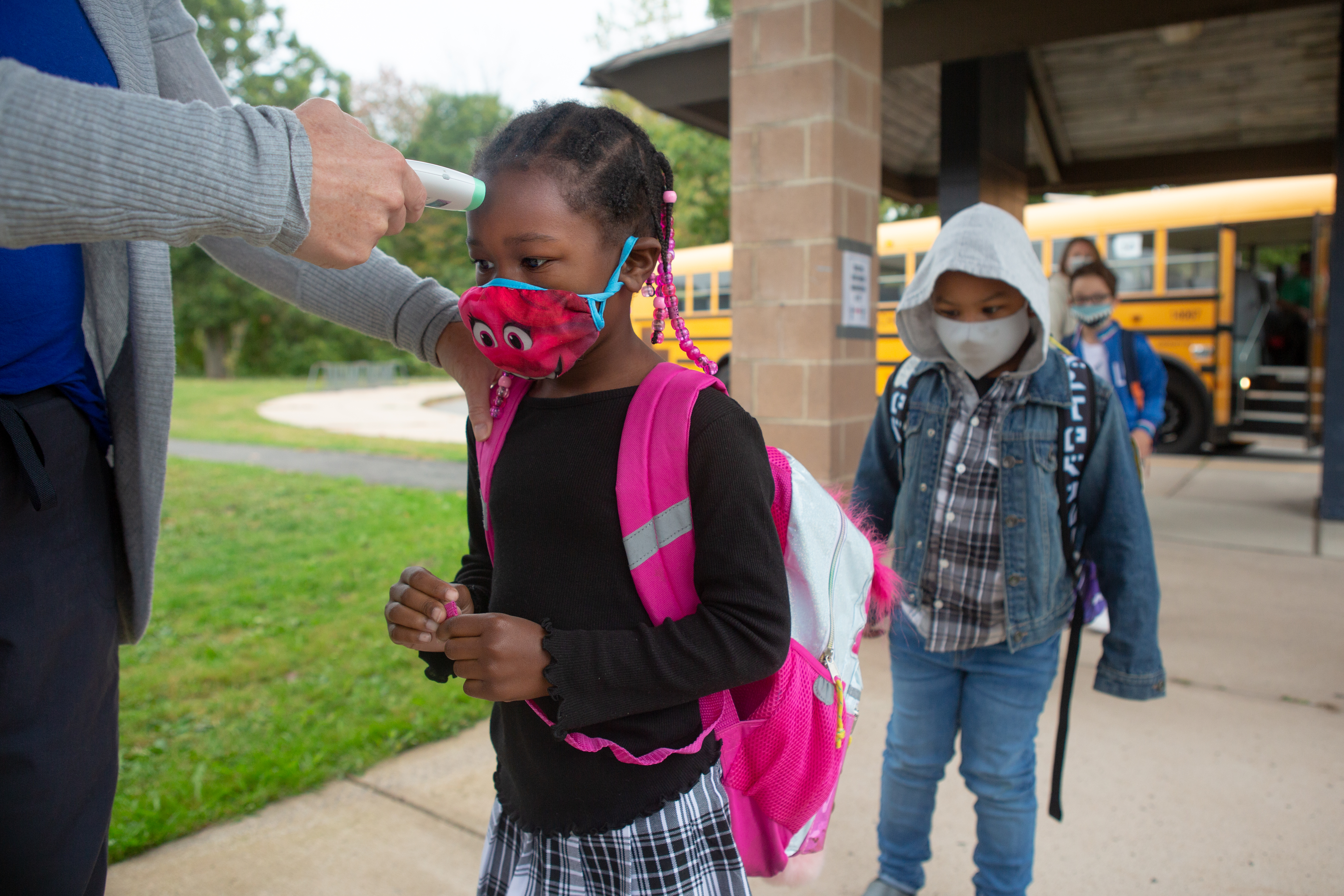 With a school bus in the background, students wearing masks and walking on a walkway receive temperature checks