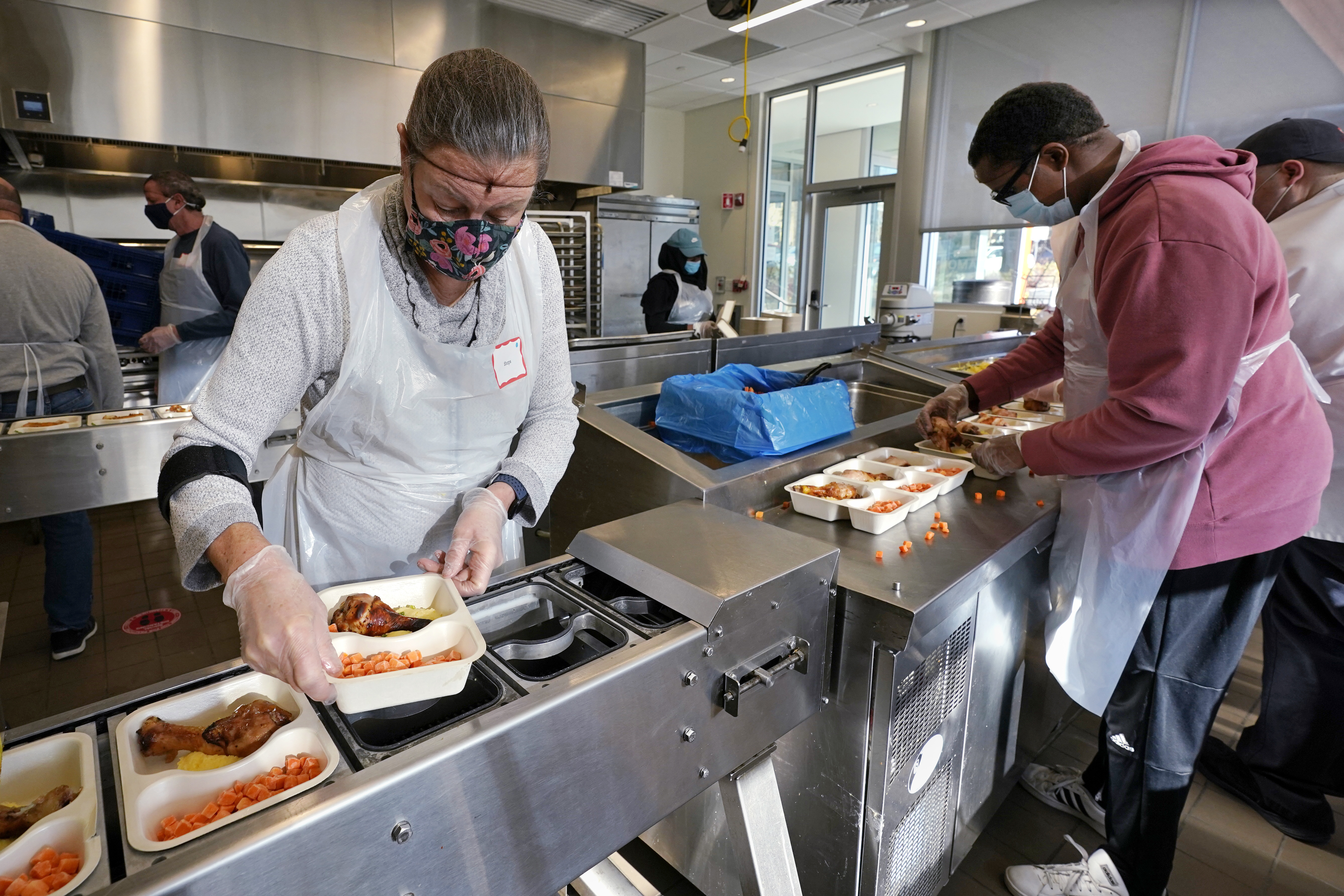 Volunteers Sheeran Howard (left) and Ibrahim Bahrr package meals at Community Servings, which prepares and delivers scratch-made, medically tailored meals to people with severe illnesses in Boston's Jamaica Plain neighborhood. Insurers first started covering Community Servings meals about five years ago, and CEO David Waters says they now cover close to 40%.