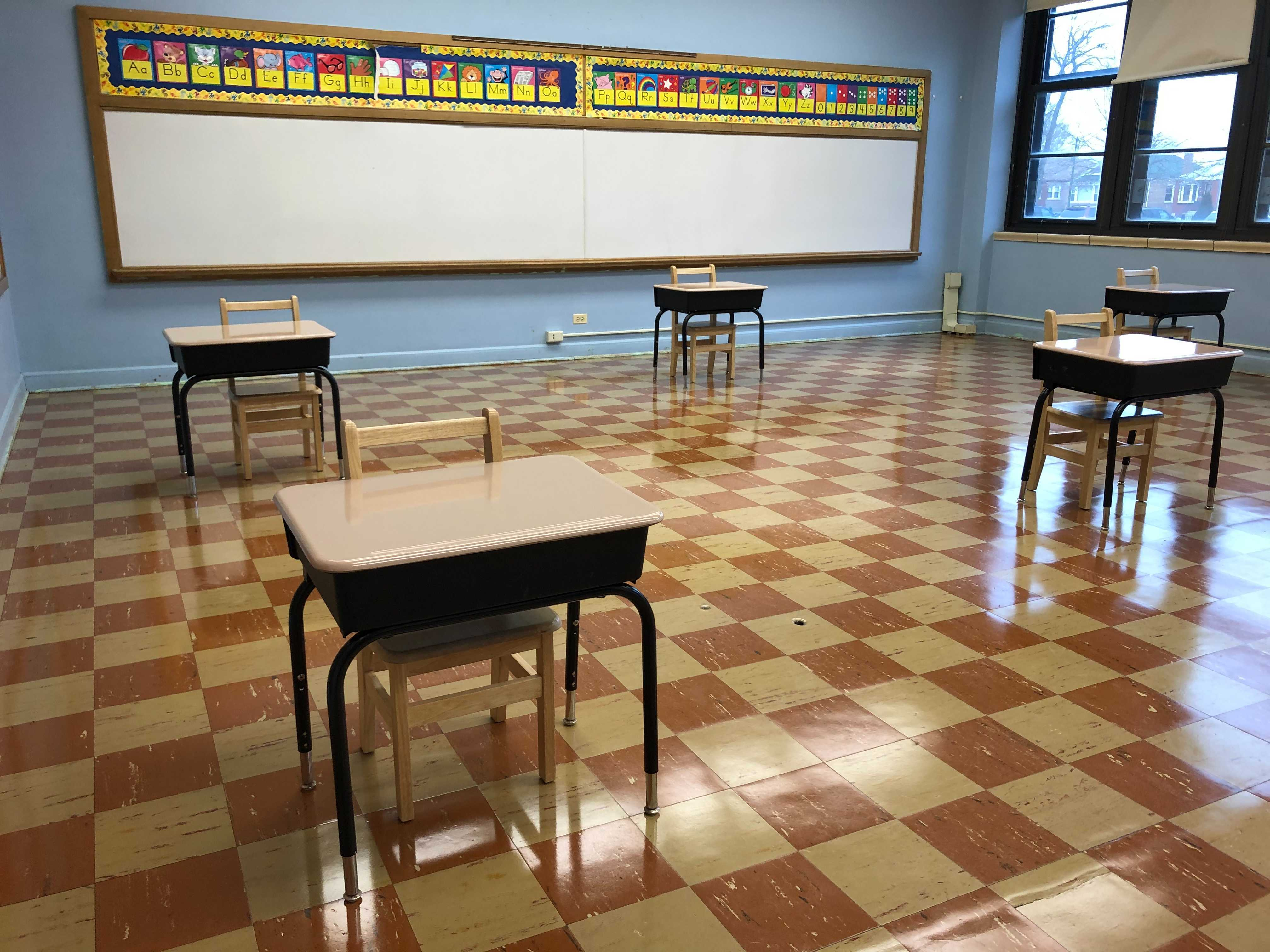An empty classroom with desks spaced out six feet apart.