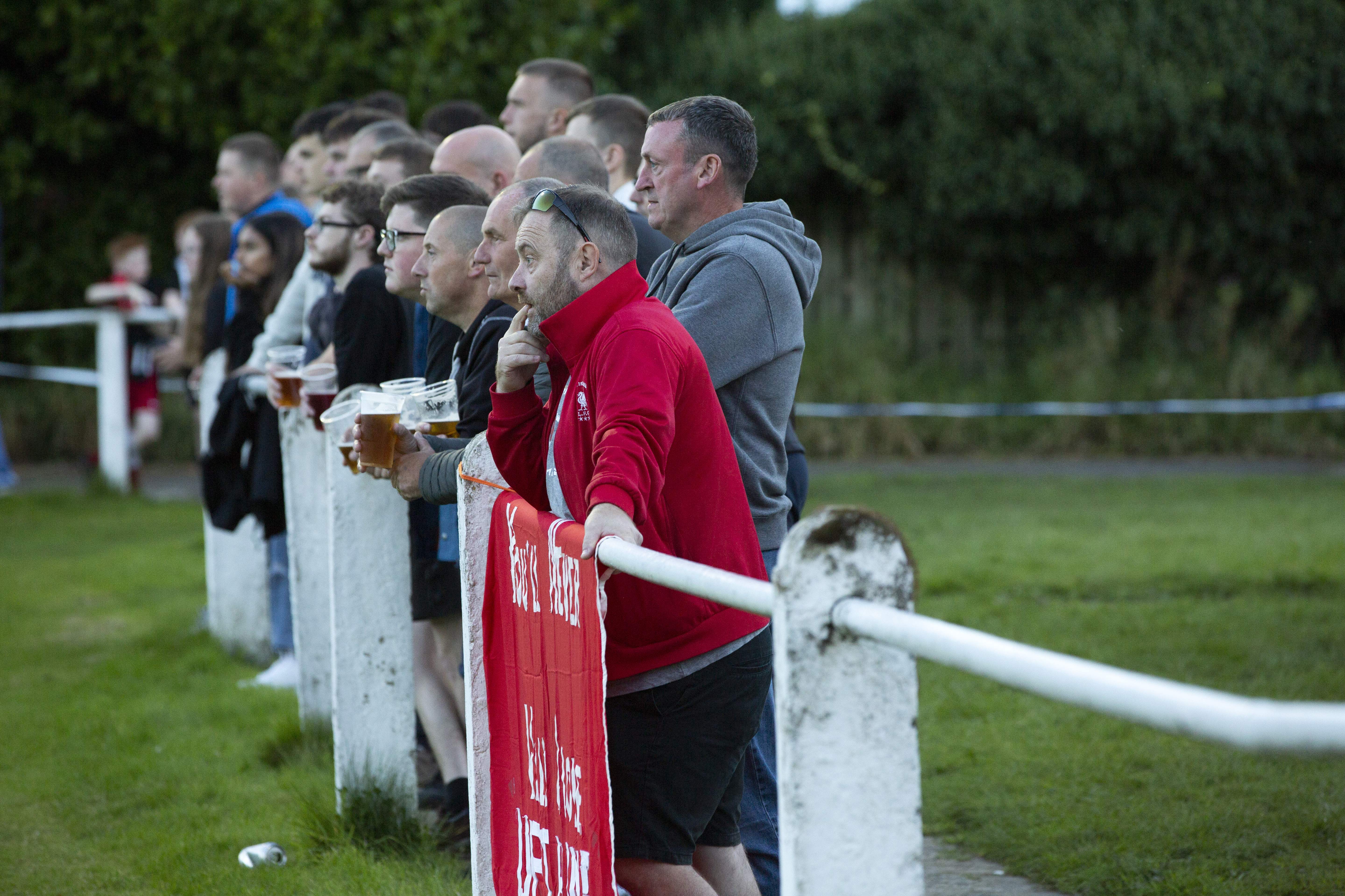 Spectators standing at the perimeter fence during the Extra Preliminary Round between Daisy Hill and Colne - New Sirs, Westhoughton - FA Cup
