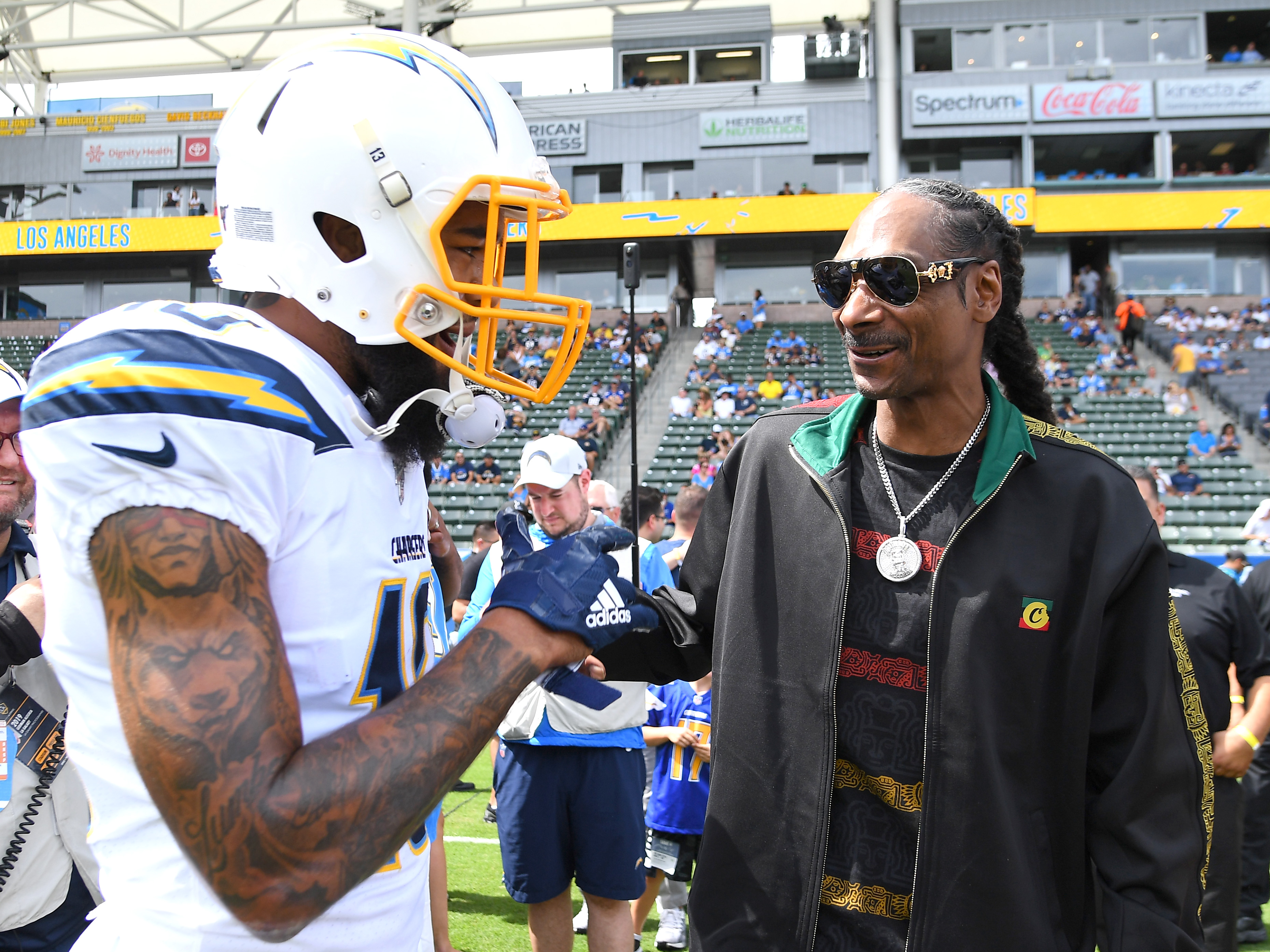 Rapper Snoop Dogg talks with wide receiver Keenan Allen #13 of the Los Angeles Chargers before the game against the Houston Texans at Dignity Health Sports Park on September 22, 2019 in Carson, California.