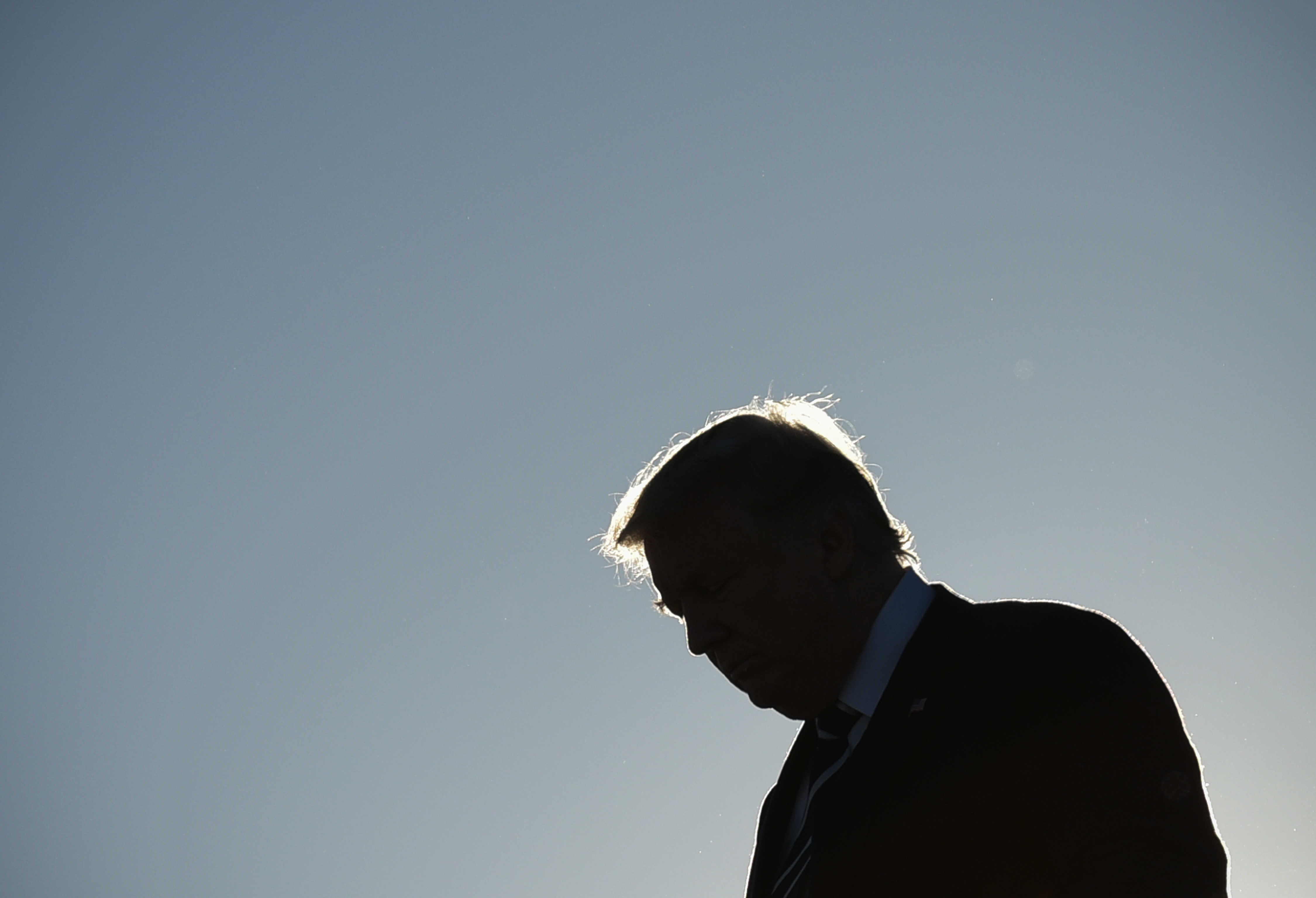 Trump's silhouette is stark against the blue sky; his face and body are in shadow; his head down, his shoulders appear slightly slumped, as the sun makes his swooping hairstyle glow slightly.