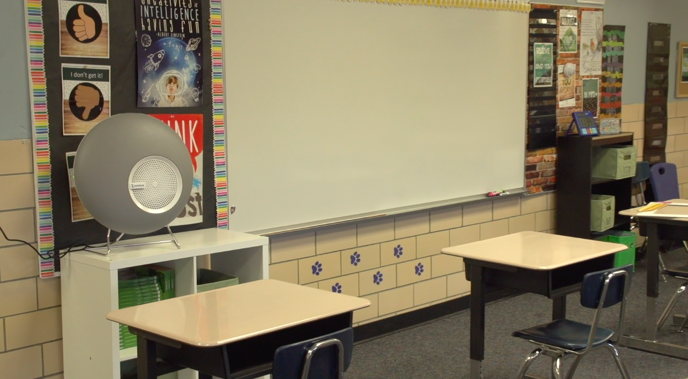 A Synexis sphere device that spread hydrogen peroxide sits on a shelf in an empty classroom.