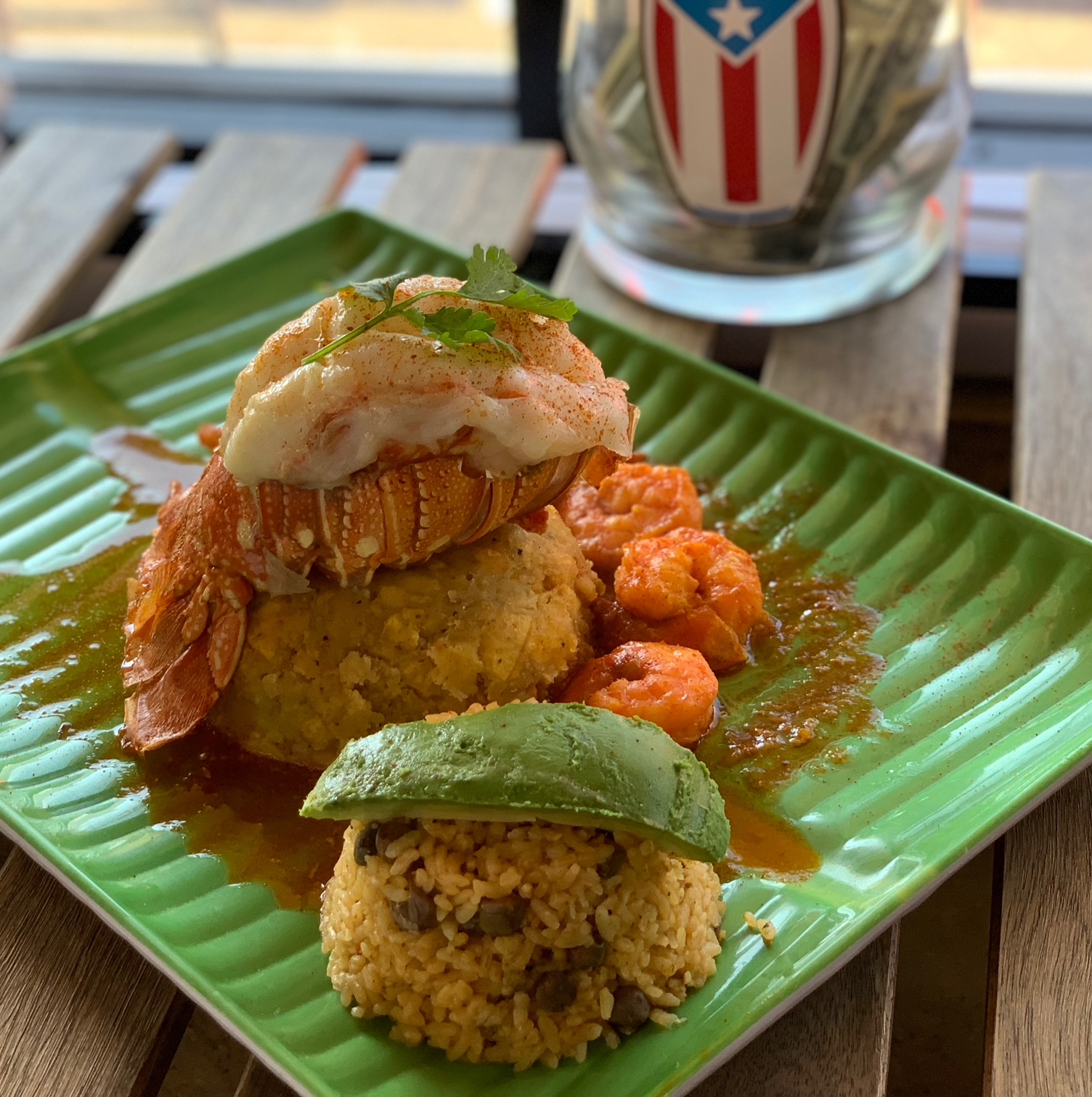 Mofongo topped with a whole lobster tail on a green plate with rice and avocado on the side