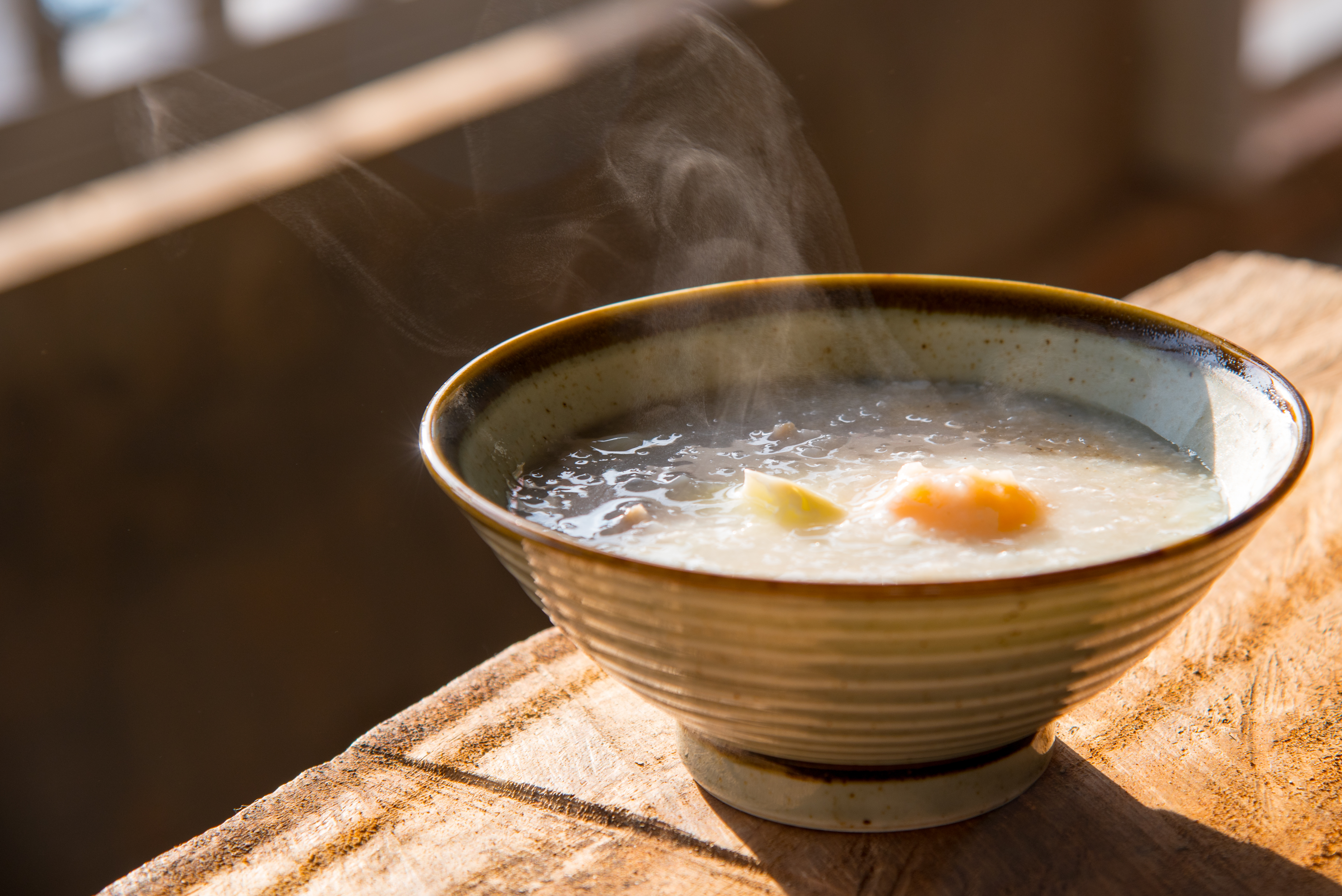 Steam rises off of beige congee served in a ceramic bowl on a light wood table.