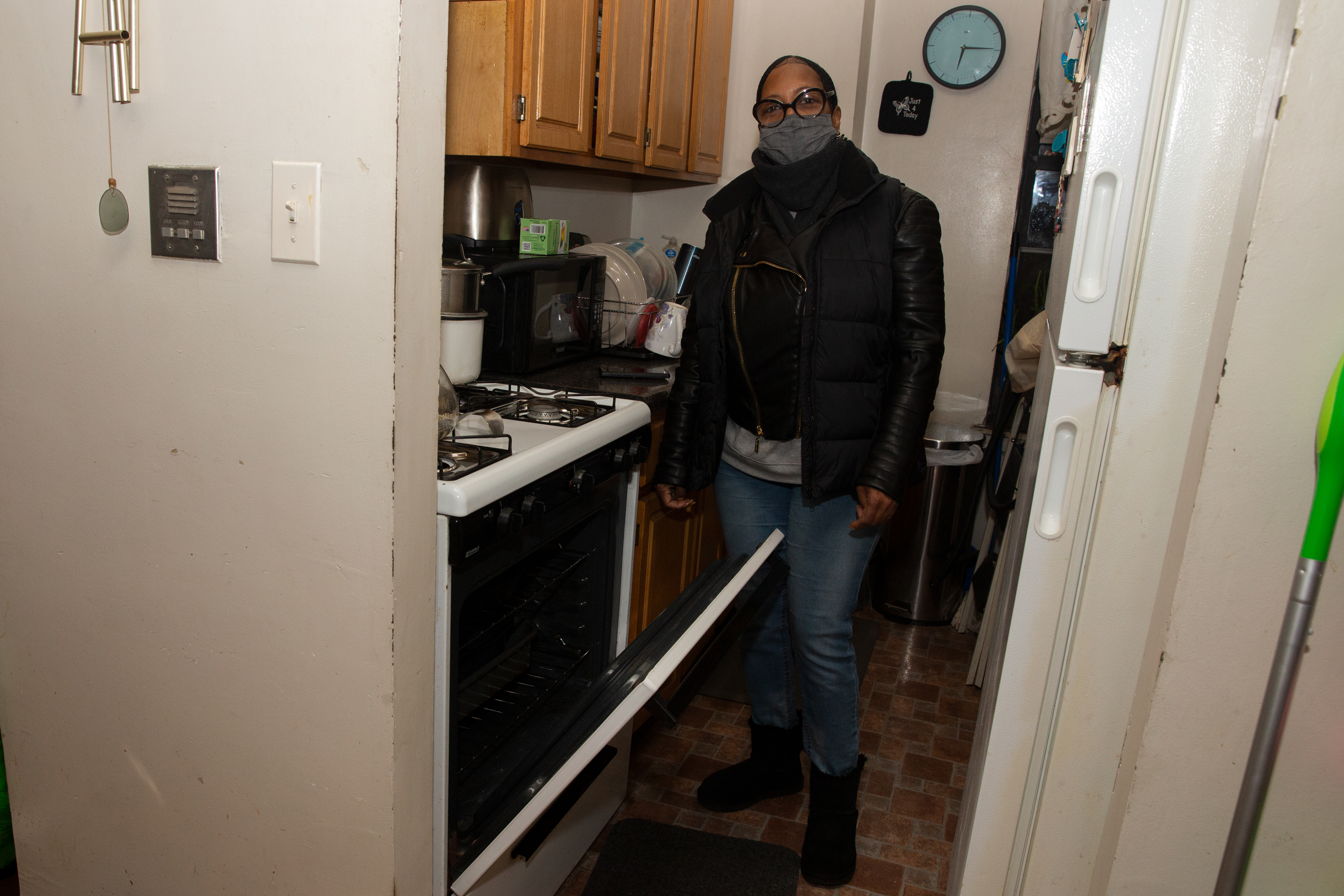 Brownsville resident Debra King uses the oven to help heat her home because the boiler in her building has not been working, Jan. 25, 2021.