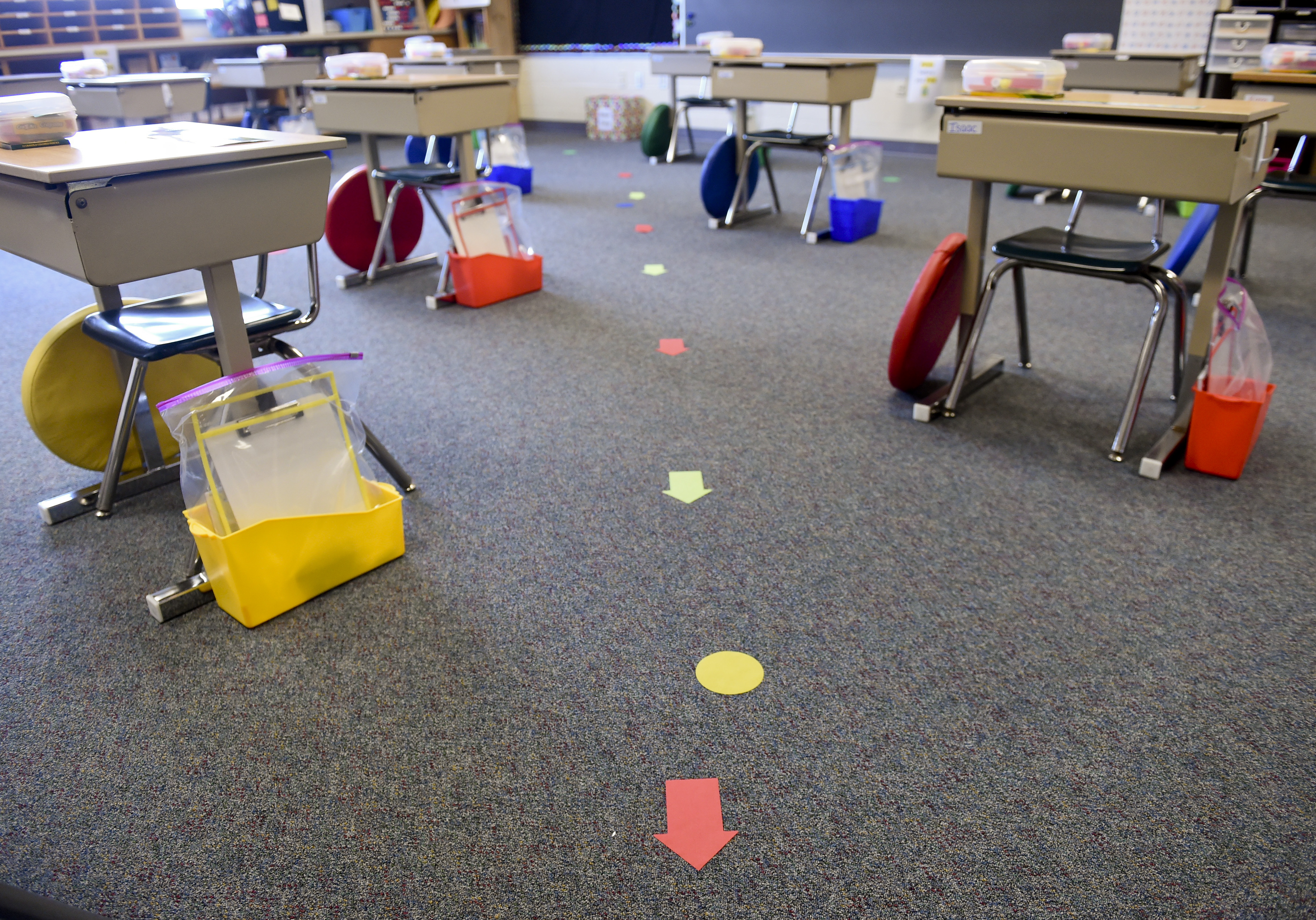 Small desks spaced 6 feet apart in a classroom, with colorful arrow stickers on the floor.