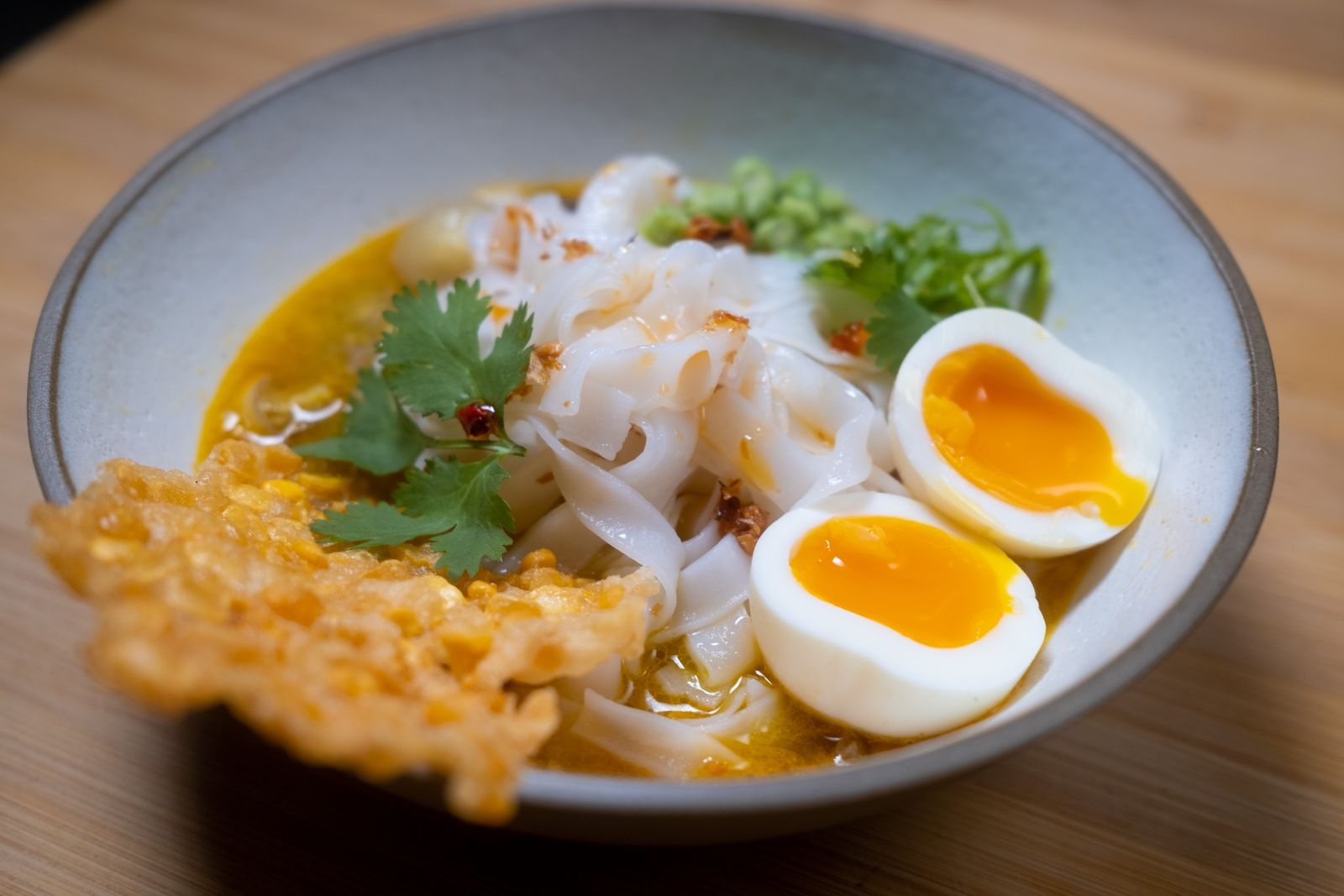 A bowl of a yellow sauce with rice noodles, with a jammy egg and fritter on the side