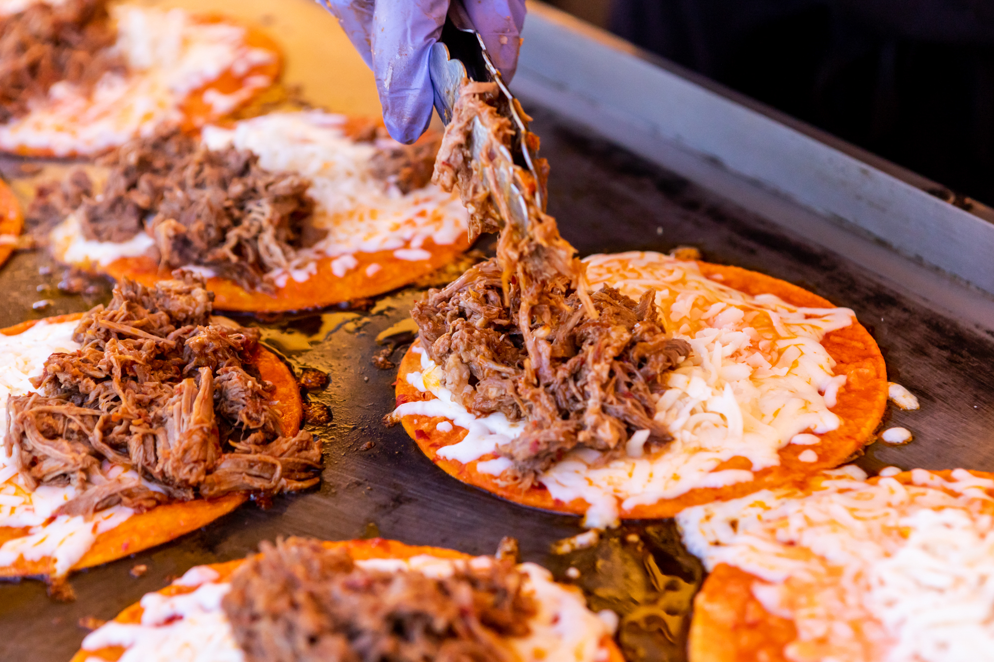 Putting birria on top of the tacos