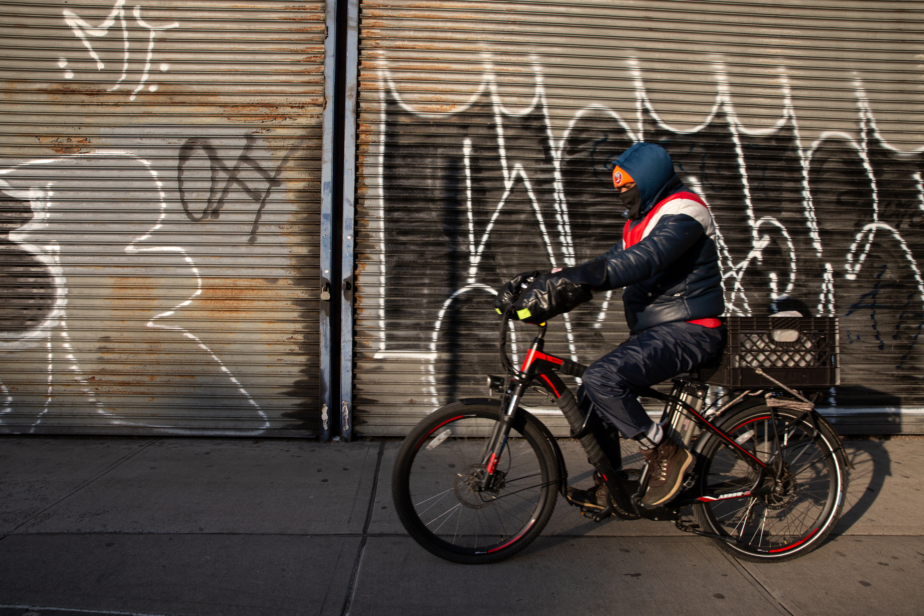 A delivery worker rides by a shuttered business in Brooklyn, Jan. 14, 2021.