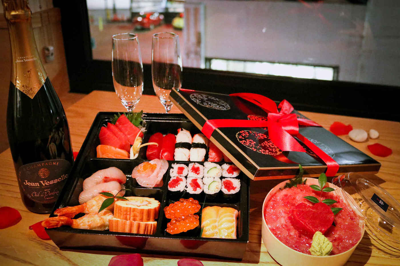 A black and white gift box revealing a selection of sushi, sitting next to two gasses of champagne and a small container with a heart-shaped piece of tuna