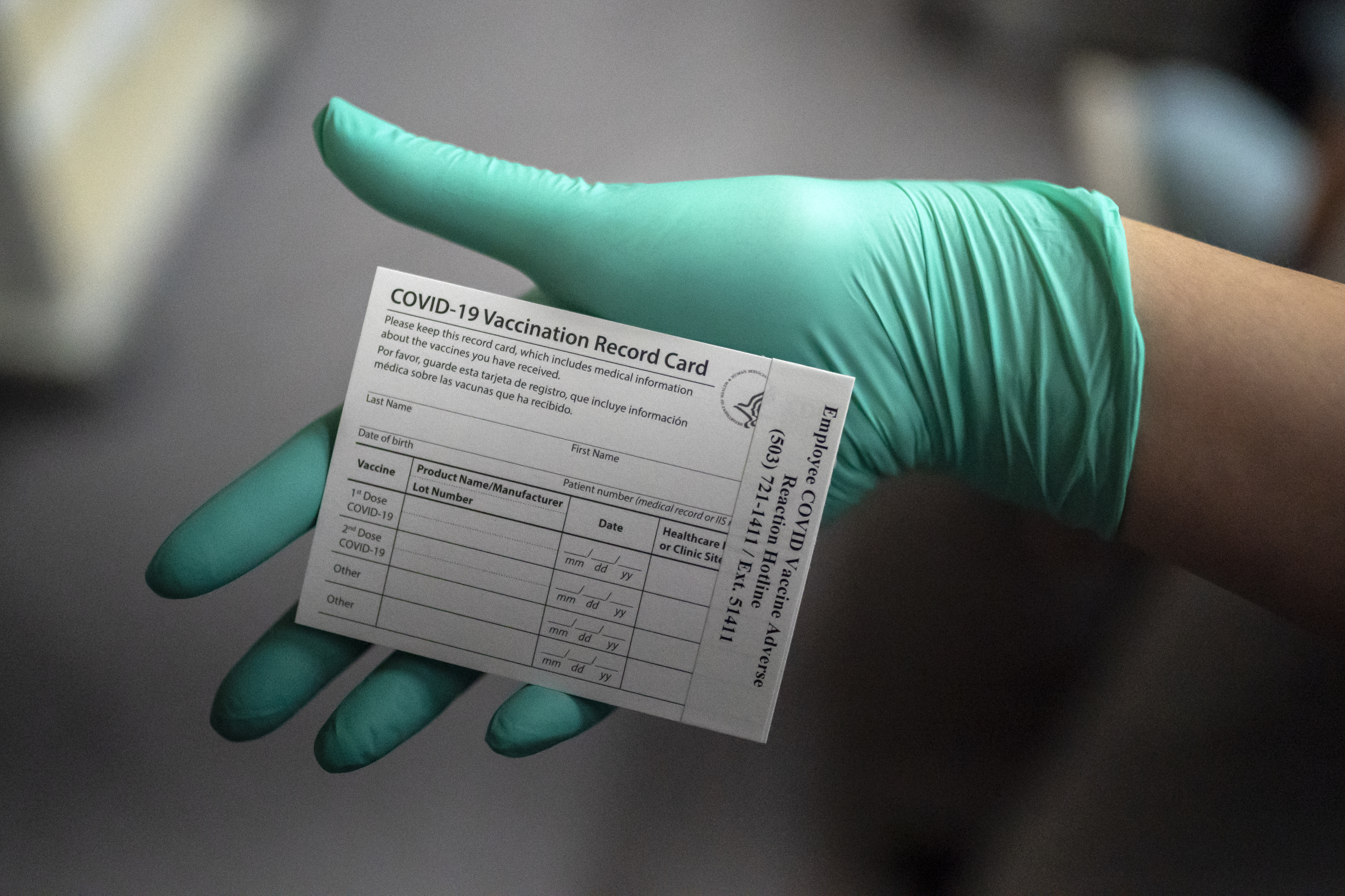 A health care worker's hand wearing a latex glove holds a Covid-19 vaccine record card at the Portland Veterans Affairs Medical Center.