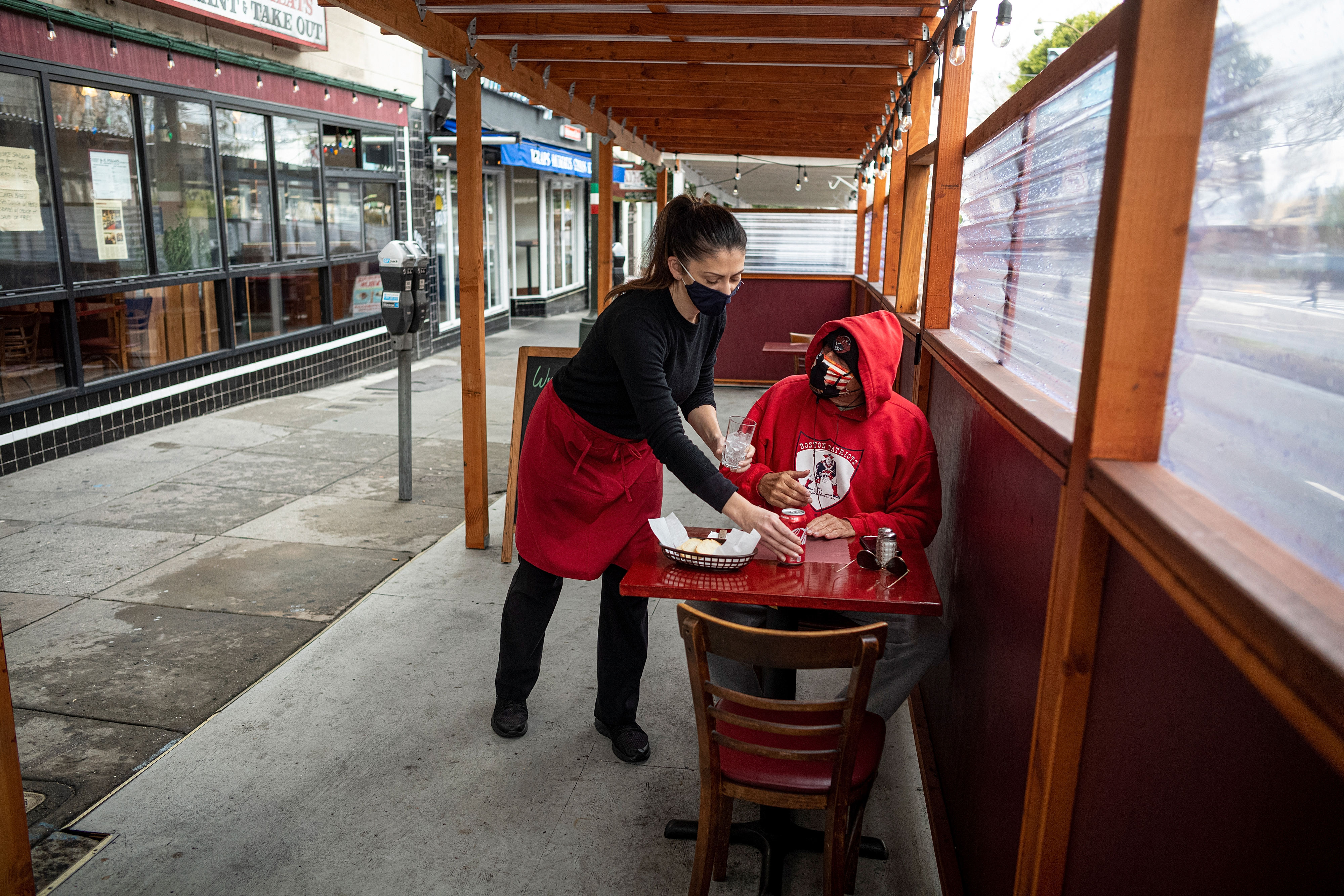 A server in a mask places food on a table in an outdoor setting