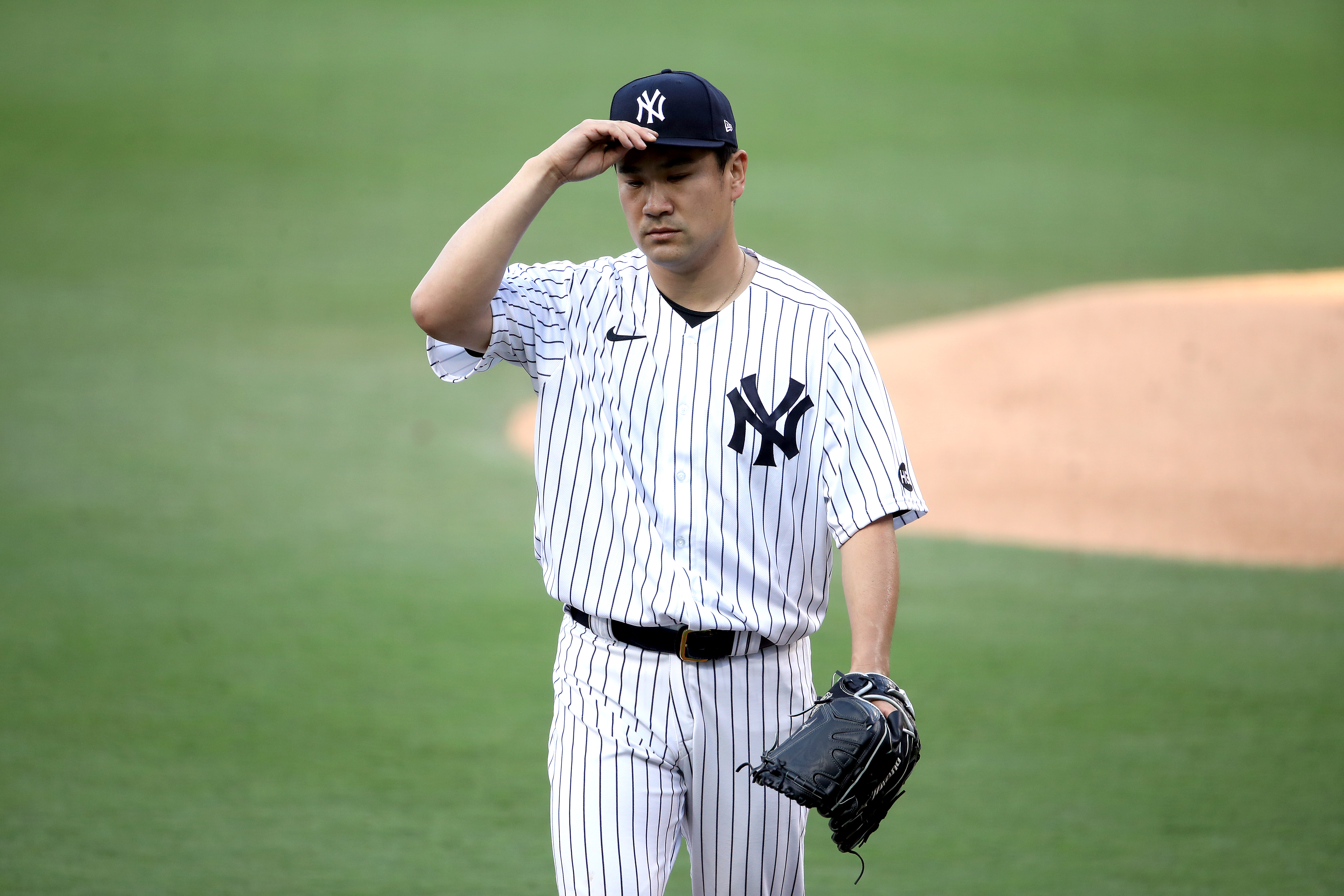 Masahiro Tanaka #19 of the New York Yankees heads back to the dugout against the Tampa Bay Rays during the second inning in Game Three of the American League Division Series at PETCO Park on October 07, 2020 in San Diego, California.