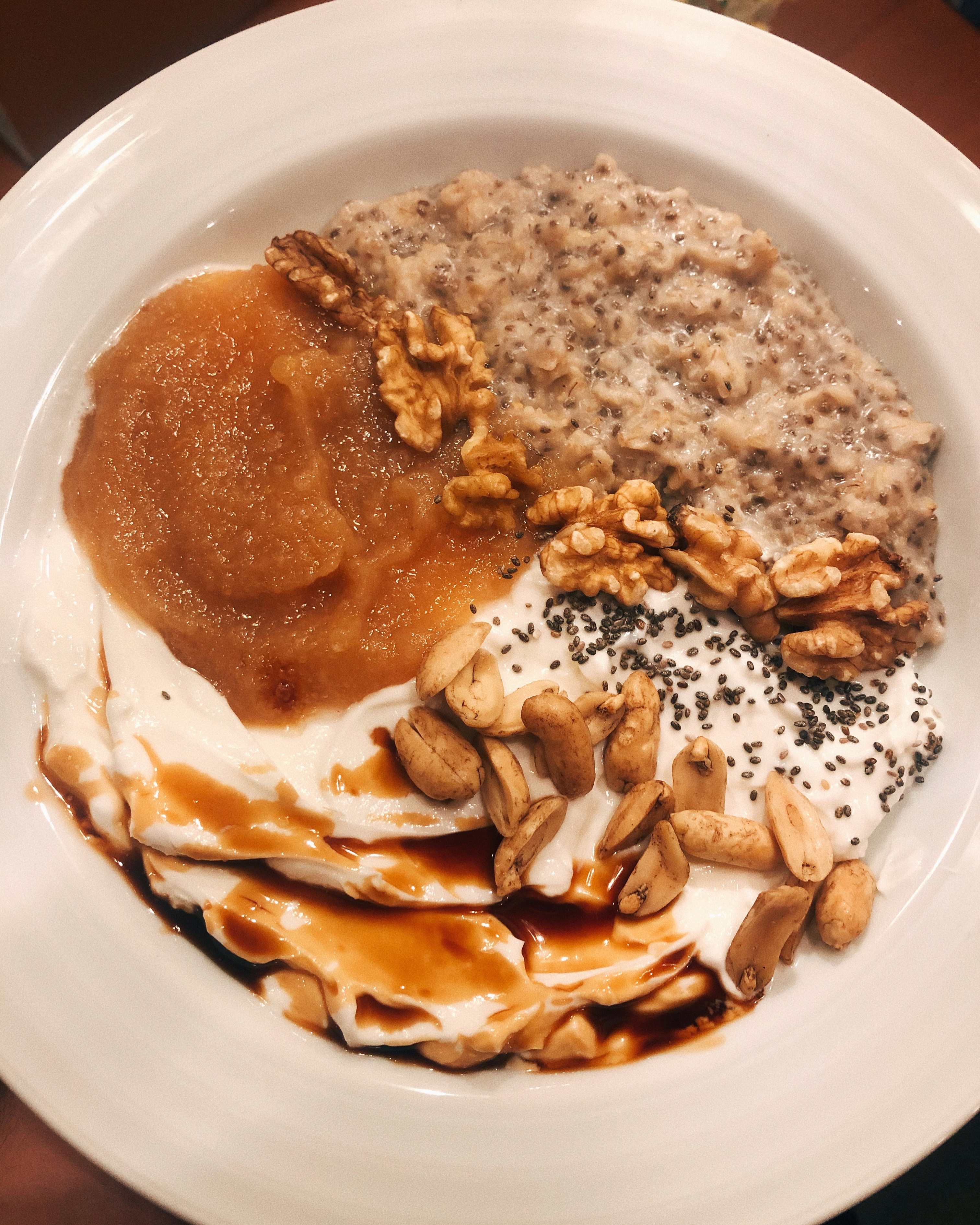 An overhead photo shows a white bowl containing oatmeal, apple sauce, yogurt, along with nuts and other toppings.