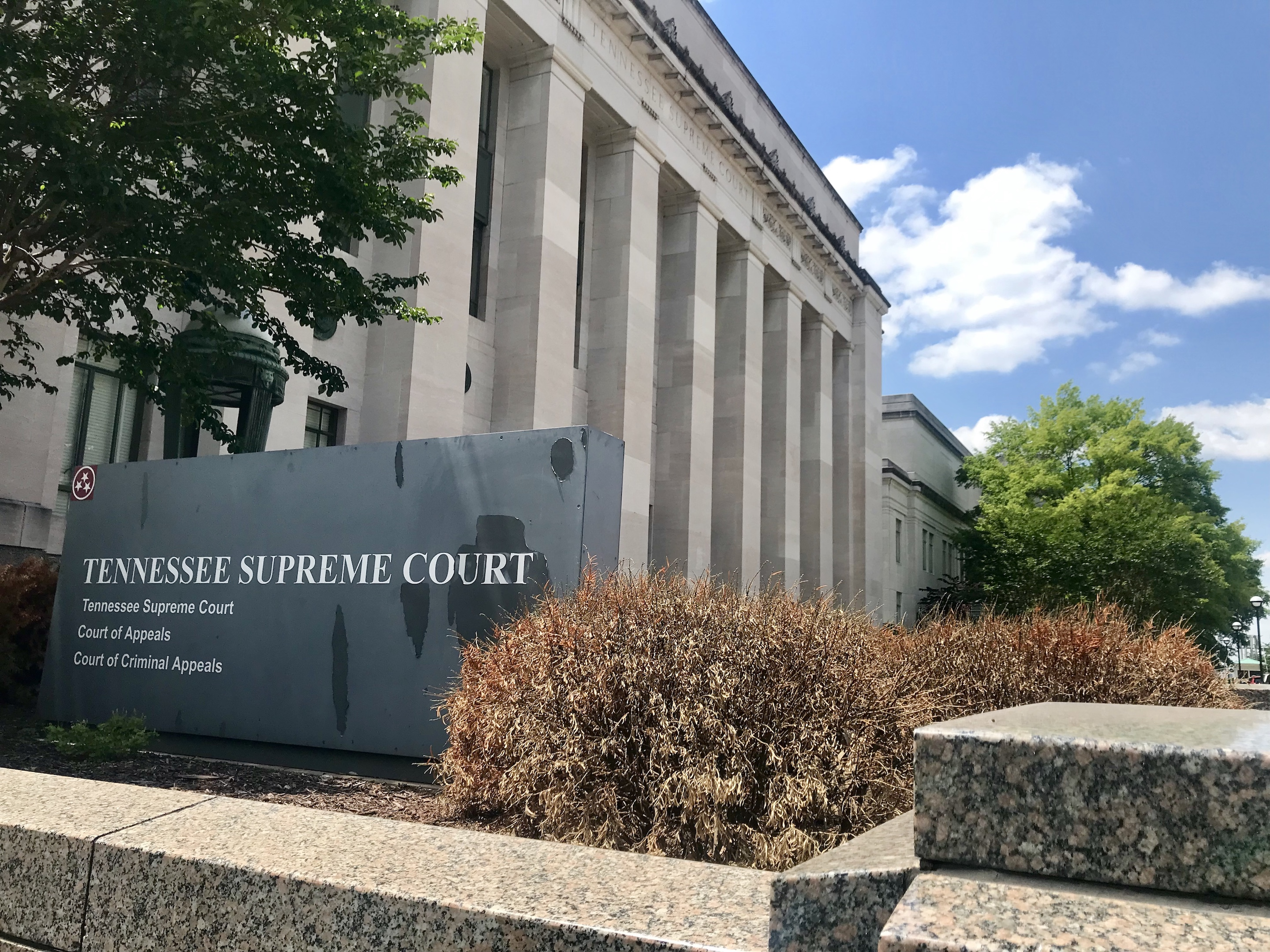 A large, multi-columned stone building set against a bright blue sky. A sign in front of the building identifies it as the Tennessee Supreme Court.