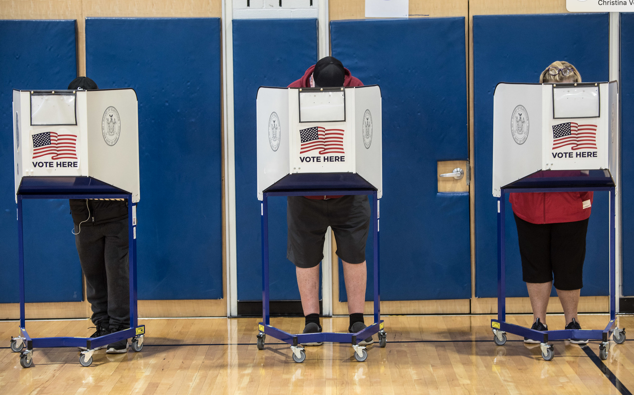 Three people stand behind voting partitions against a blue divider.