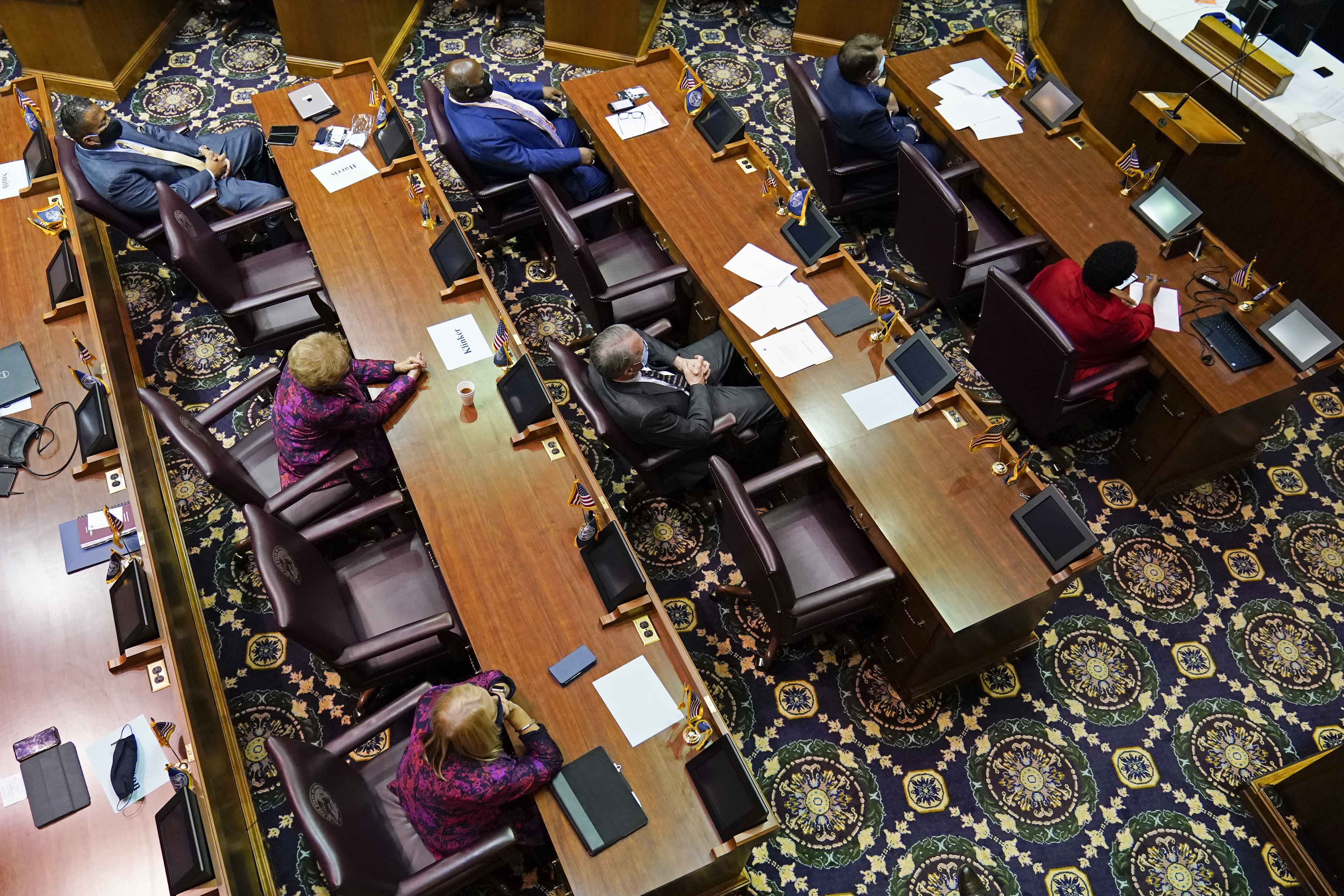 View looking down on the floor of the Indiana House, with people sitting at desks, separated by empty seats