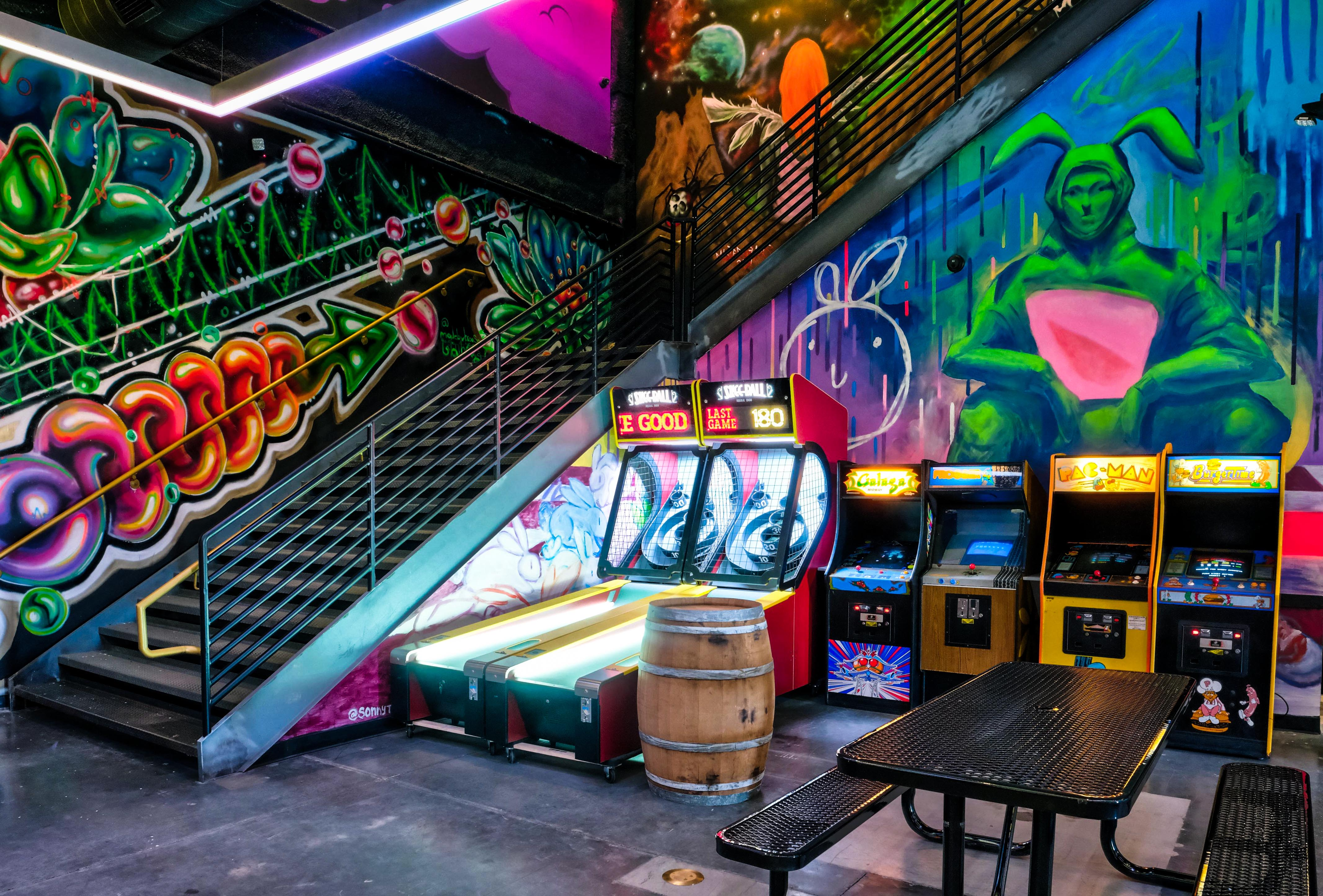 A graffiti-lined staircase with video games and a metal picnic table at Emporium Arcade Bar