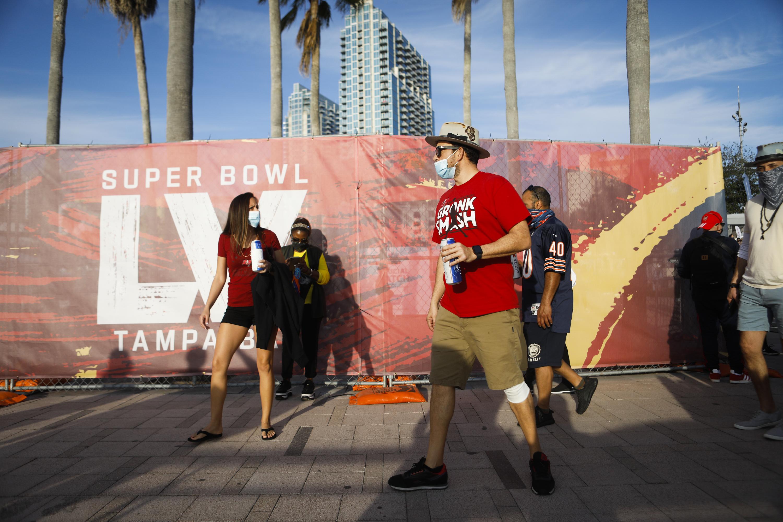 """Pedestrians walk past a wall that reads """"Super Bowl 55."""""""