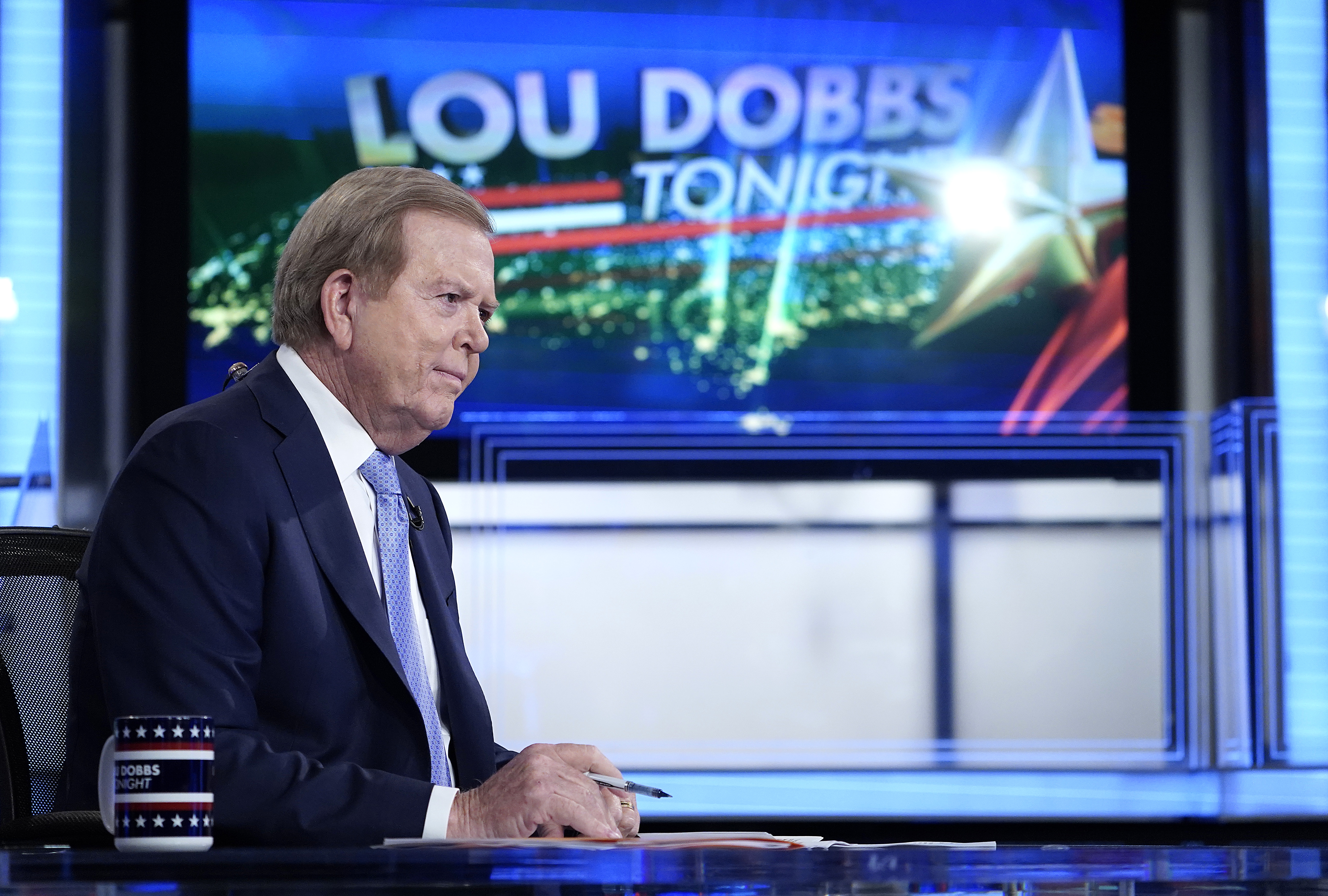 """Dobbs, in a navy suit, white shirt, and blue tie, his brown and gray hair swept back, sits at a desk in front of a screen that says in bold letters, """"Lou Dobbs Tonight."""""""