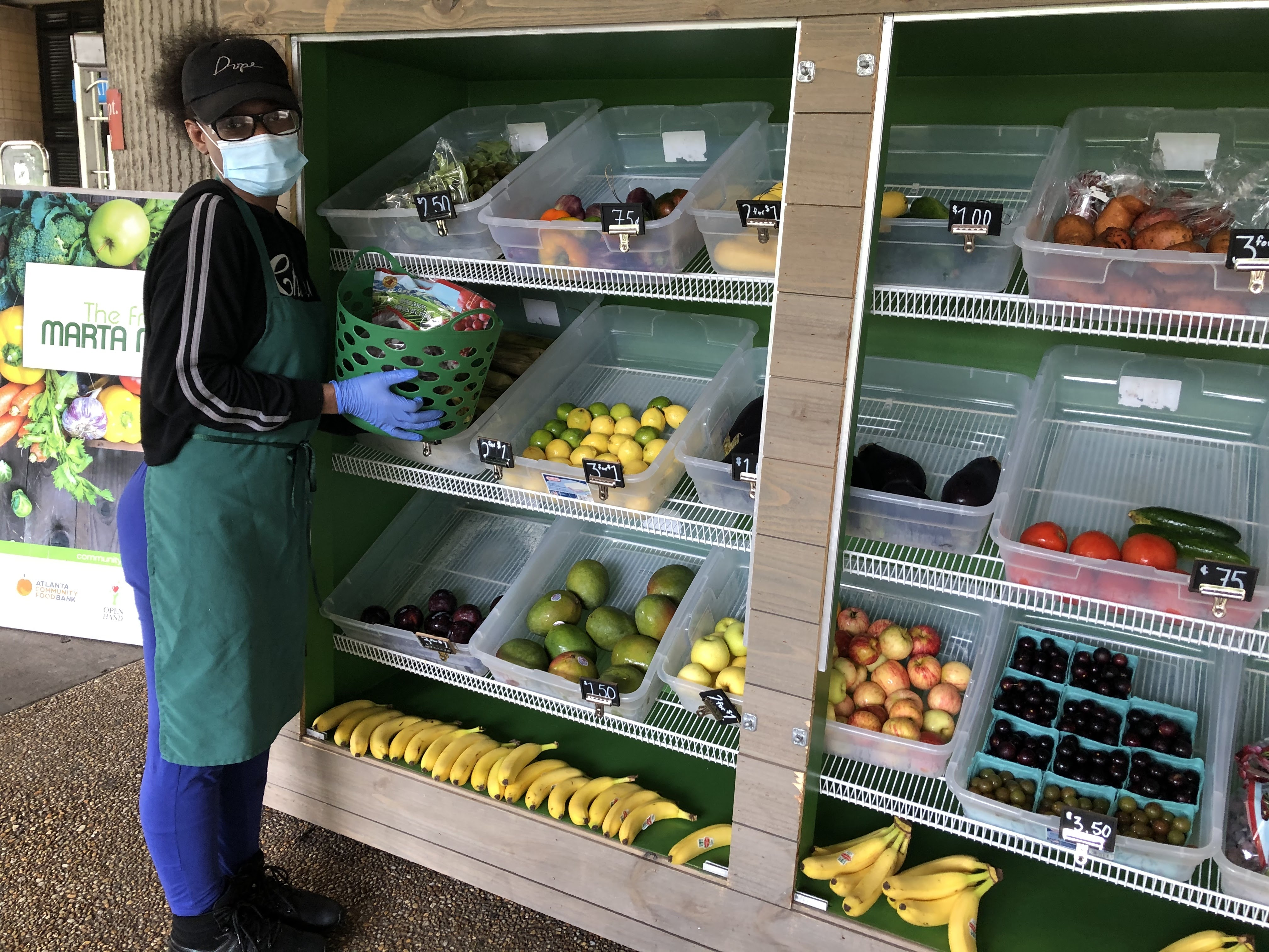 A woman in eye glasses wearing a face mask, blue rubber gloves, a black sweatshirt, jeans, and a green apron tends to the farm stand at an Atlanta MARTA rail station