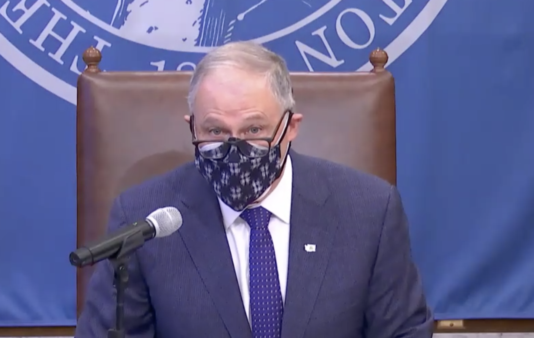 Gov. Jay Inslee at a press conference wearing a face mask, a blue suit, and glasses