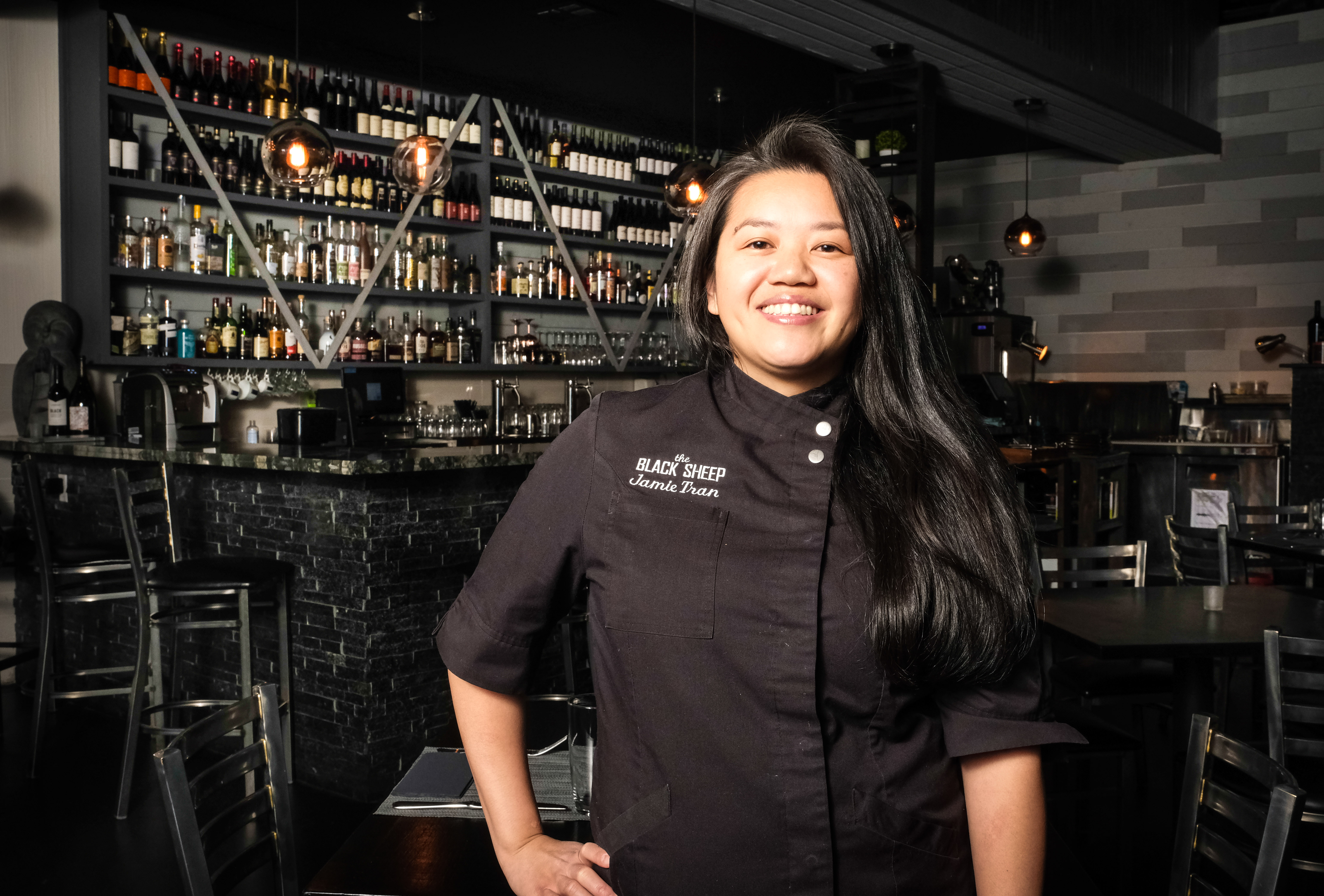 A woman in a jack chef's coat stands in front of a bar