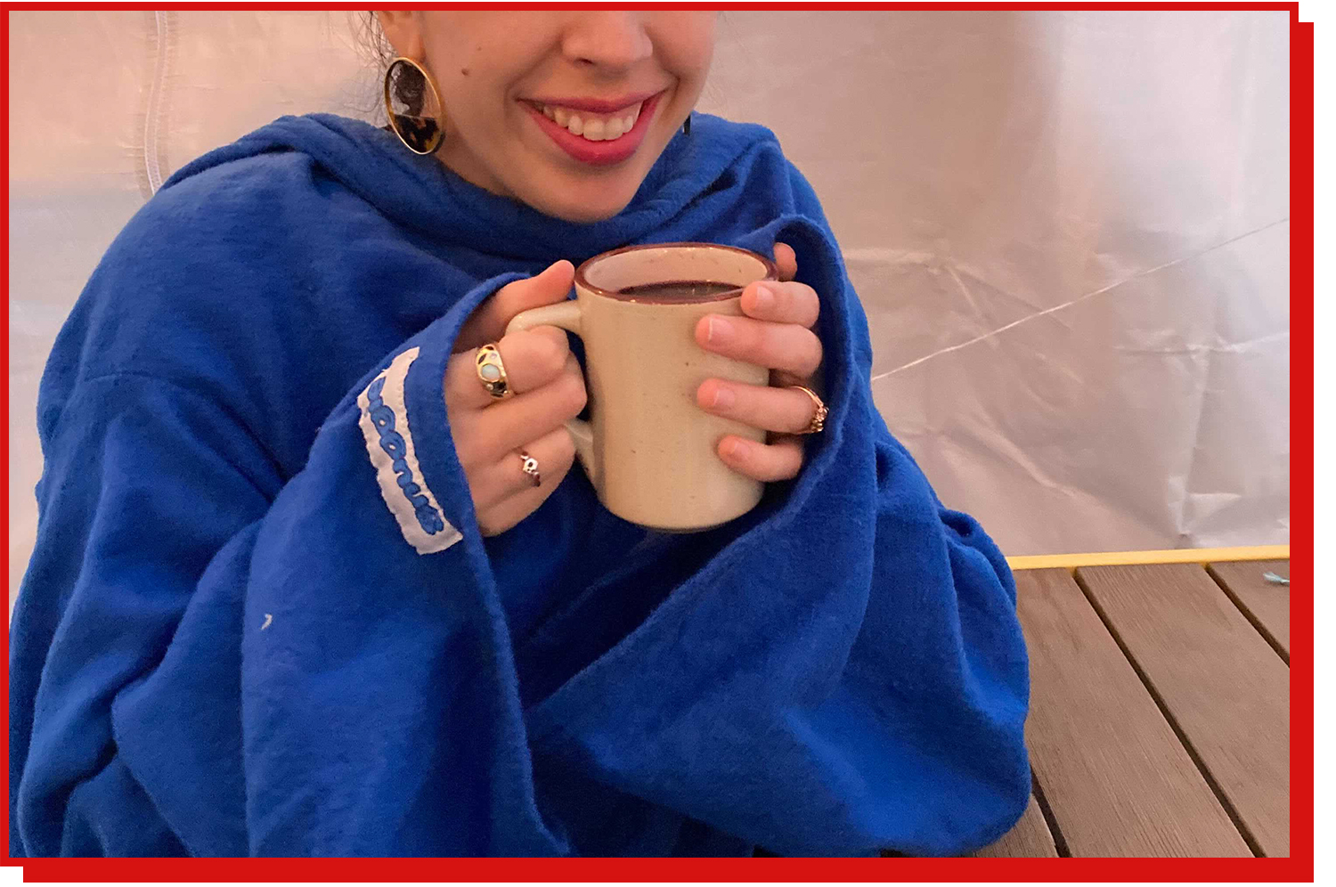 Smiling woman wearing blue Snuggie holding a mug containing a warm beverage.
