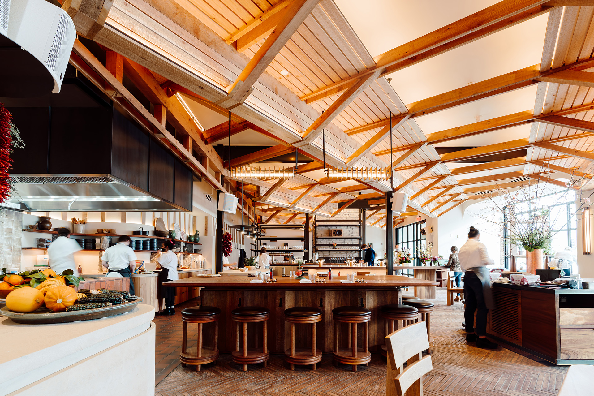 The view of the sun-filled dining room and bar. Lots of blonde wood, vaulted ceilings with soaring beams. A small bar is at the center of the room with a few stools and in the background are several, soft focused staff members in white shirts and black pants.