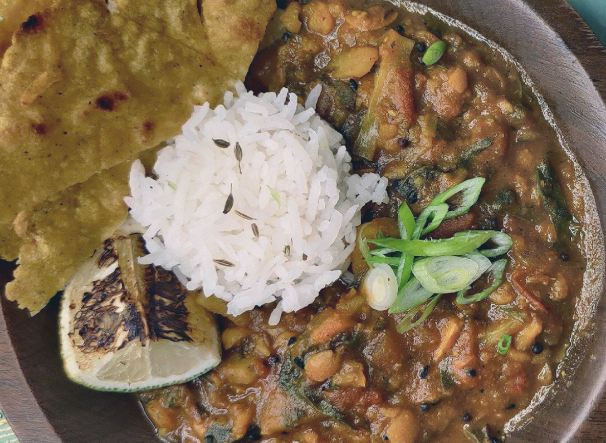 Black-eyed pea masala with a scoop of jeera rice in the center garnished with green onions, a seared lime, and naan