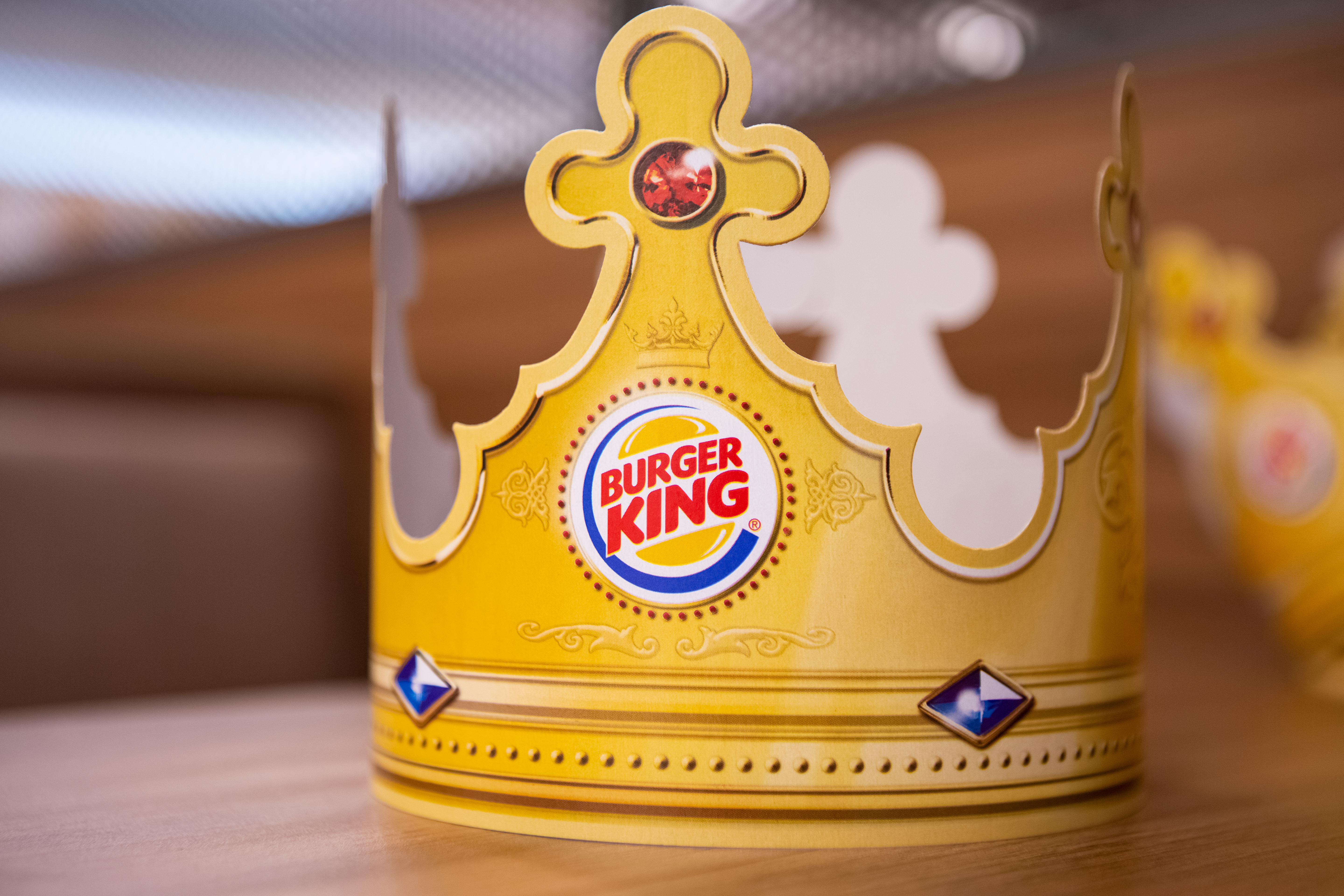 Paper Burger King Crown On Wooden Table Surface On Interior Fast Food Restaurant Background