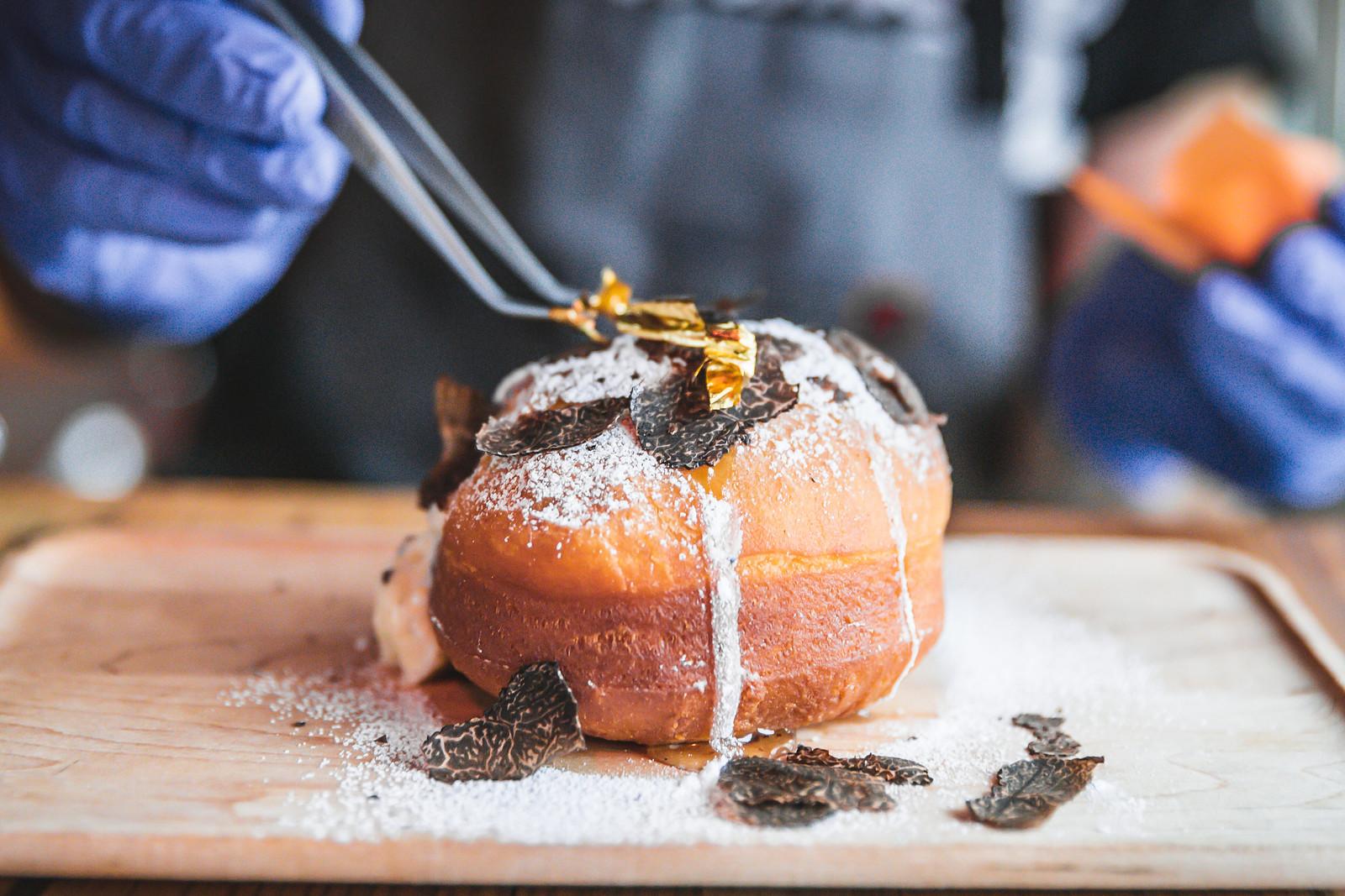 Tweezers top a powder doughnut with edible gold.