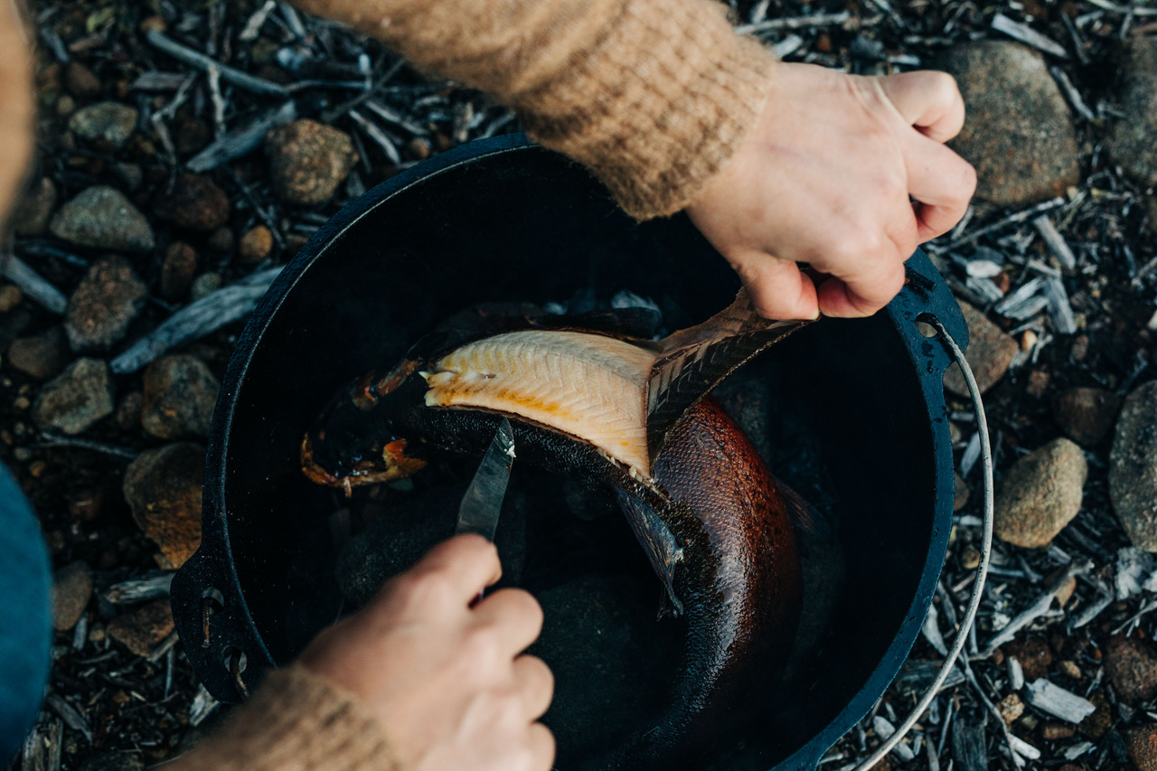 A pair of hands peels the skin off a piece of fish in a bucket