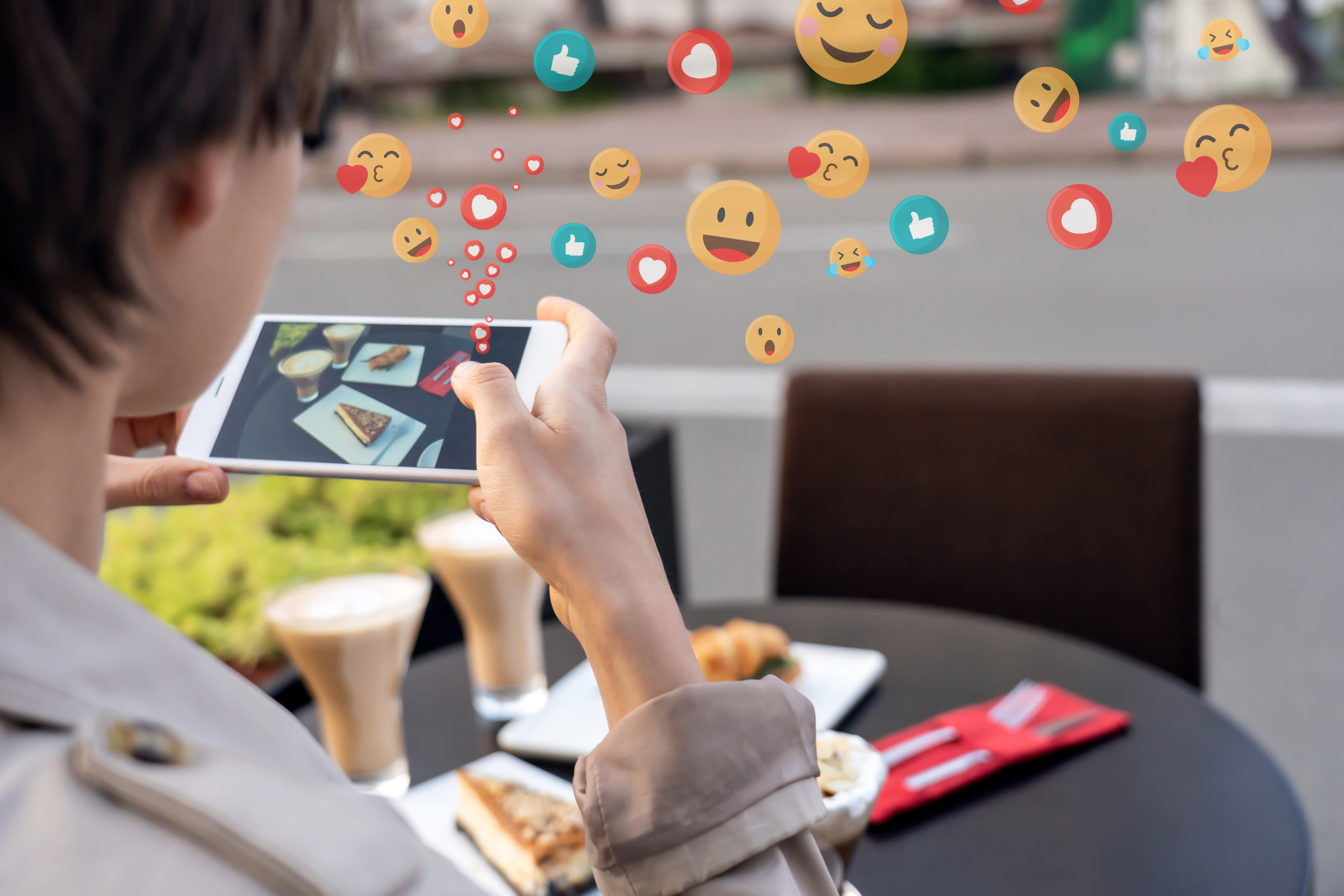 A person taking a photo with a phone of food with emoji rising as reactions.