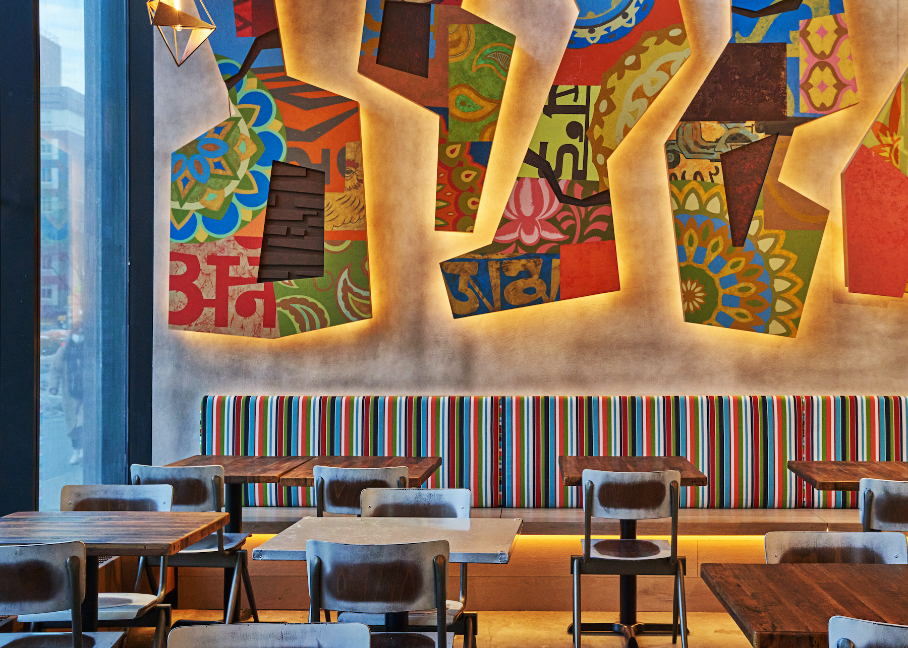 The interior of the restaurant Dhamaka with murals on the wall