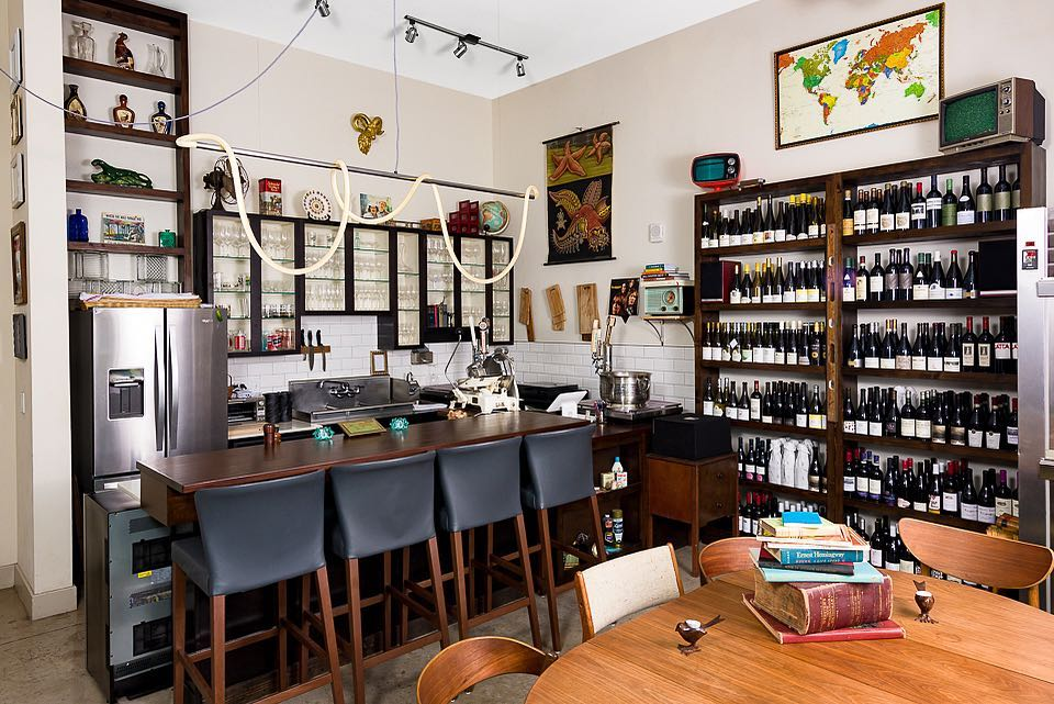 The inside of a wine bar, with a four-seat bar and a large wooden table, and a bookcase full of bottles of wine