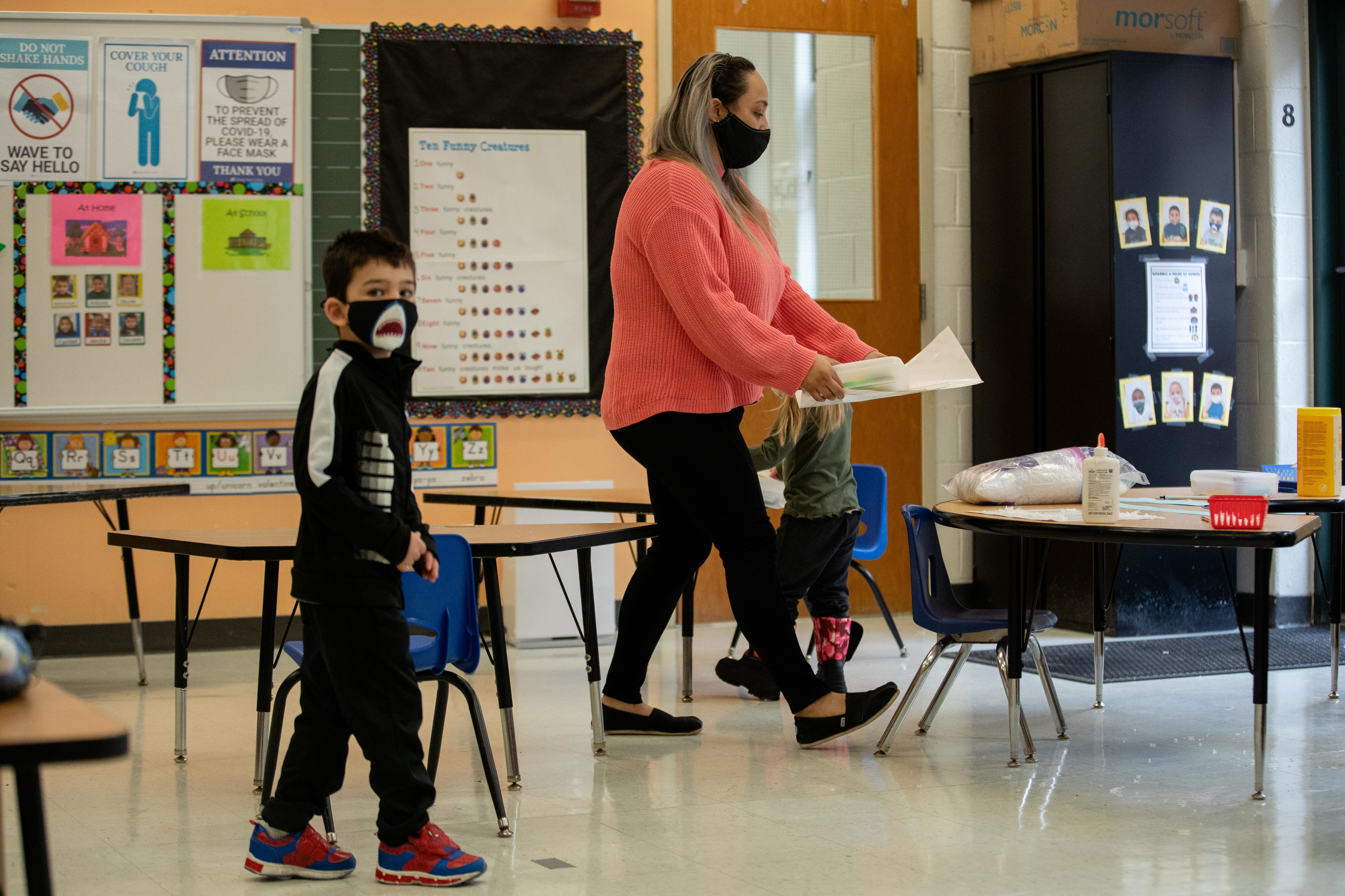 A teacher and a student walk across a classroom at Jordan Community Elementary School in the Rogers Park neighborhood, Friday morning, Jan. 15, 2021.