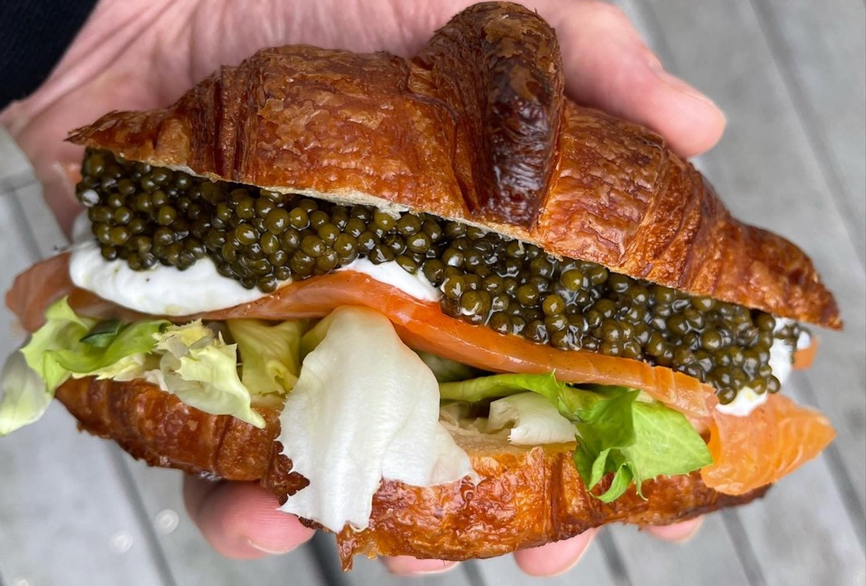 A croissant stuffed with smoked salmon, cheese, lettuce, and caviar