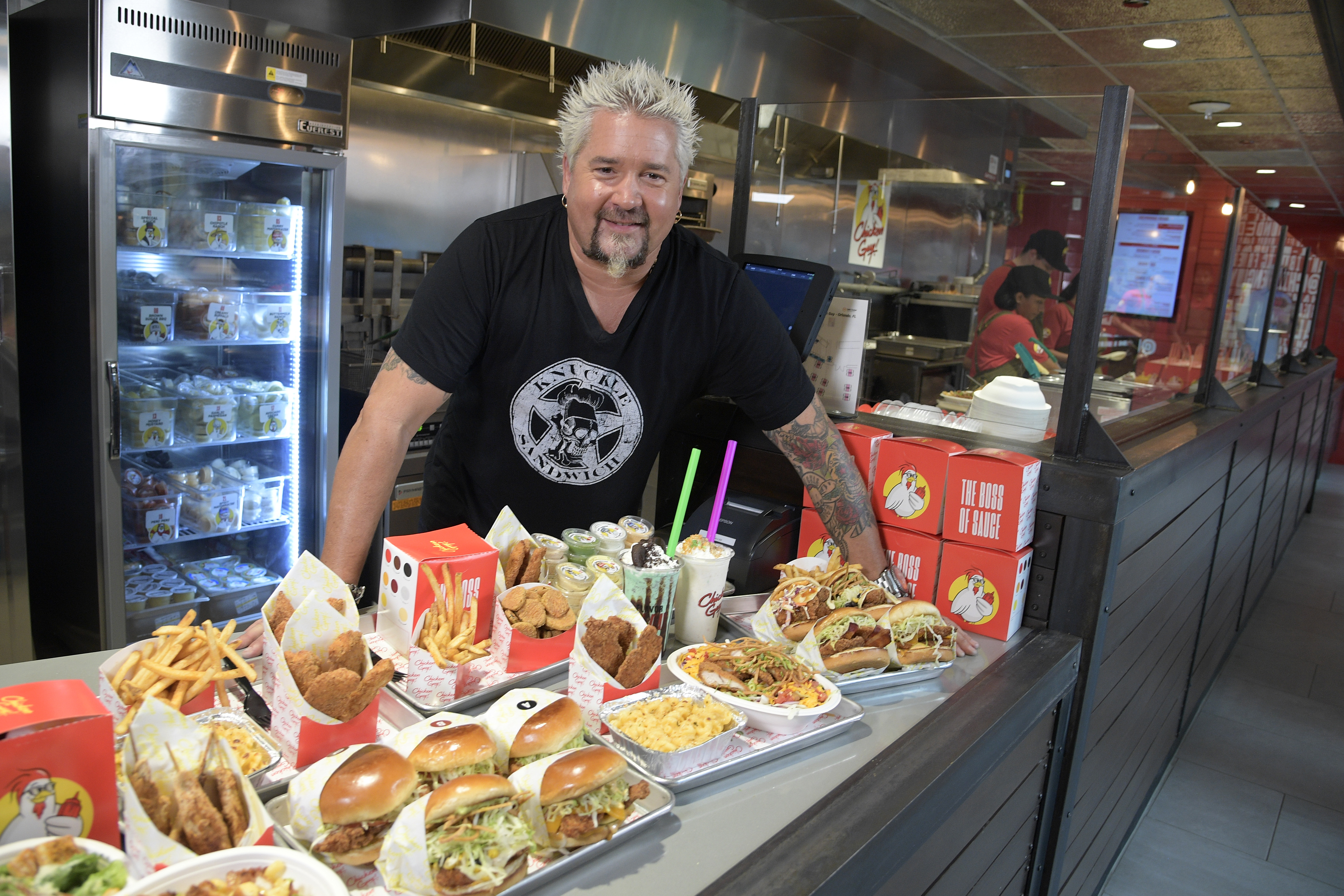 Guy Fieri poses with dishes from Chicken Guy, which opened at FedEx Field in Maryland before the COVID-19 pandemic.