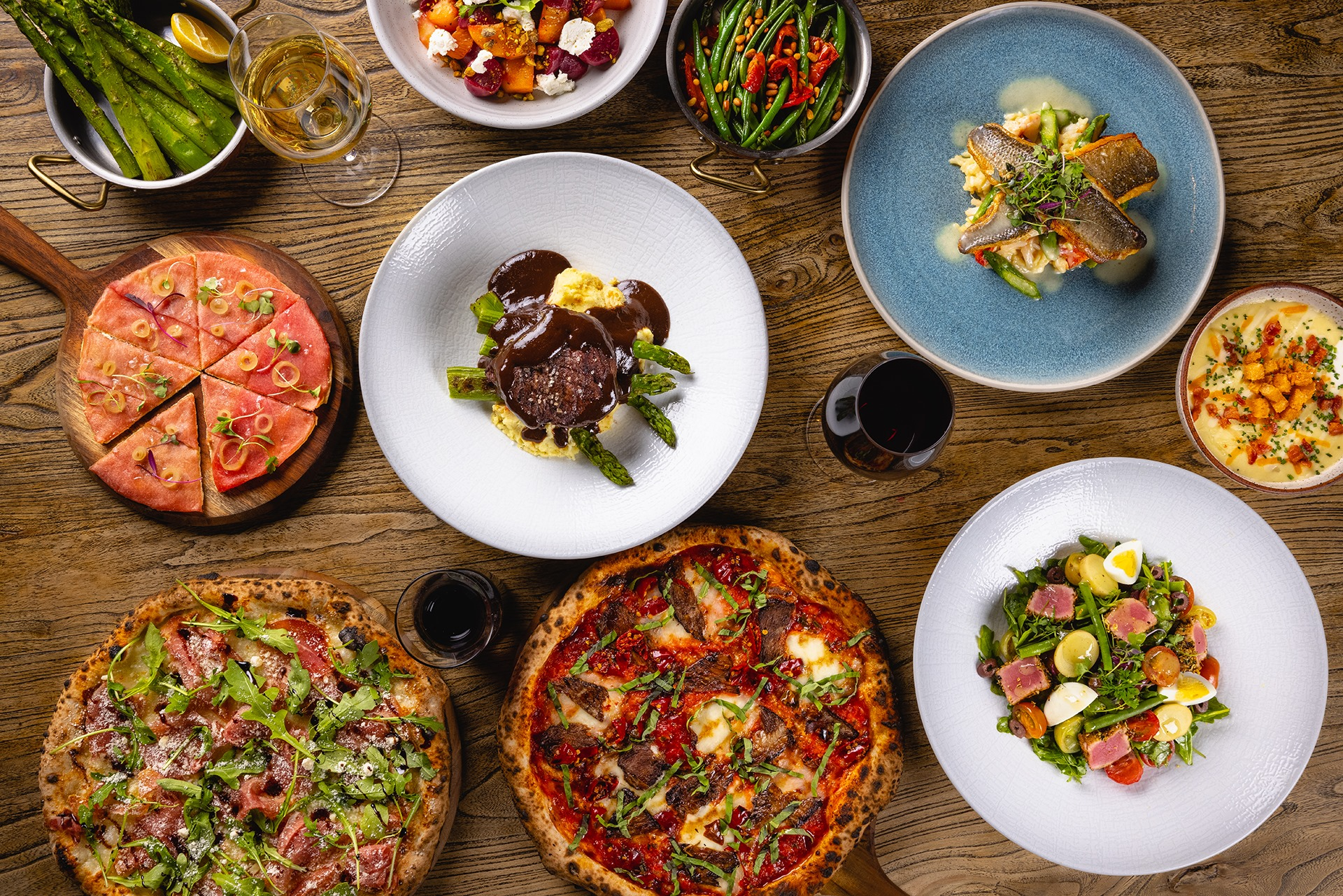 An overhead view of pizzas, a pasta dish, beef, and more on a wood table